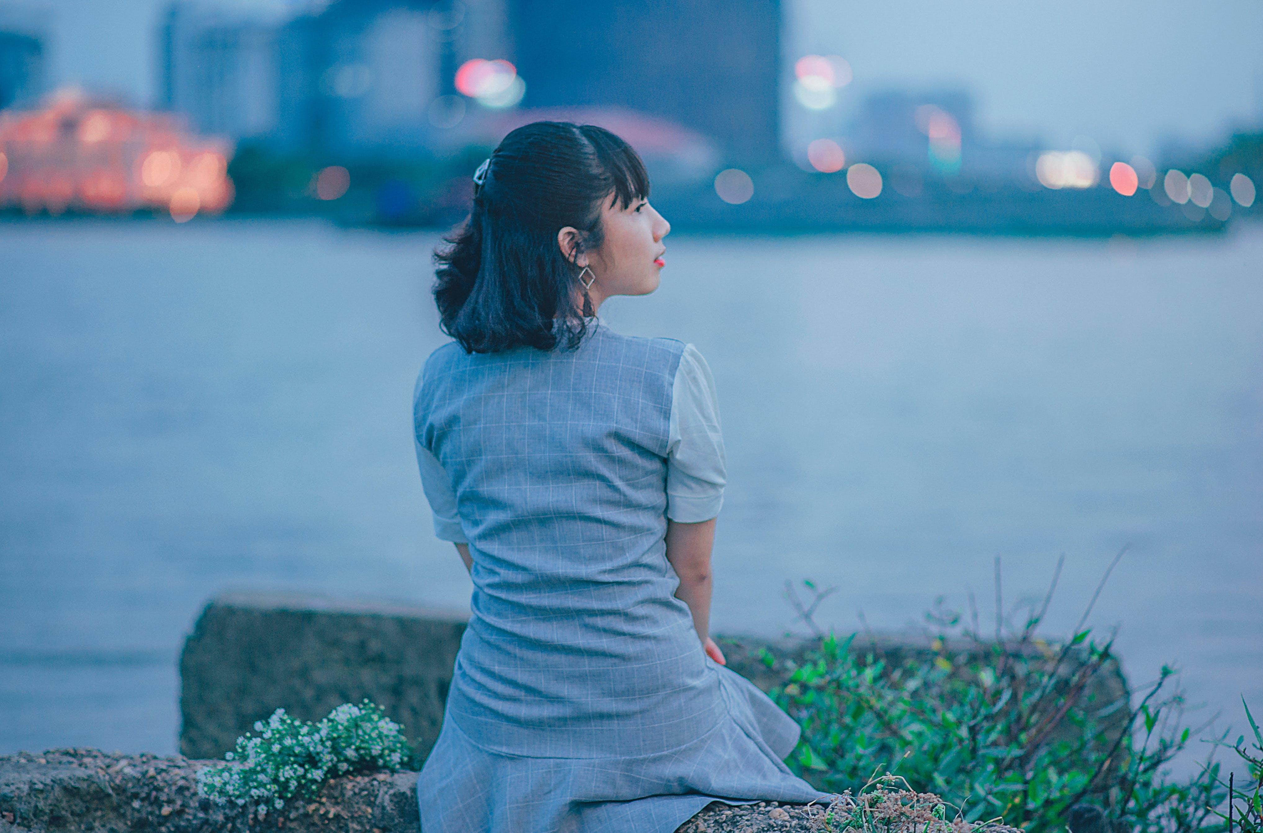 Woman Wearing Gray Dress Sitting Near Body of Water