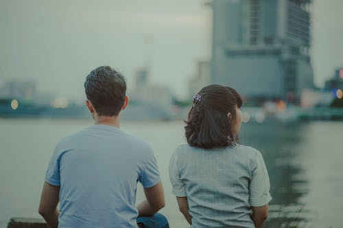 Selective Focus Photography of Man and Woman Watching Body of Water and Concrete Buildings