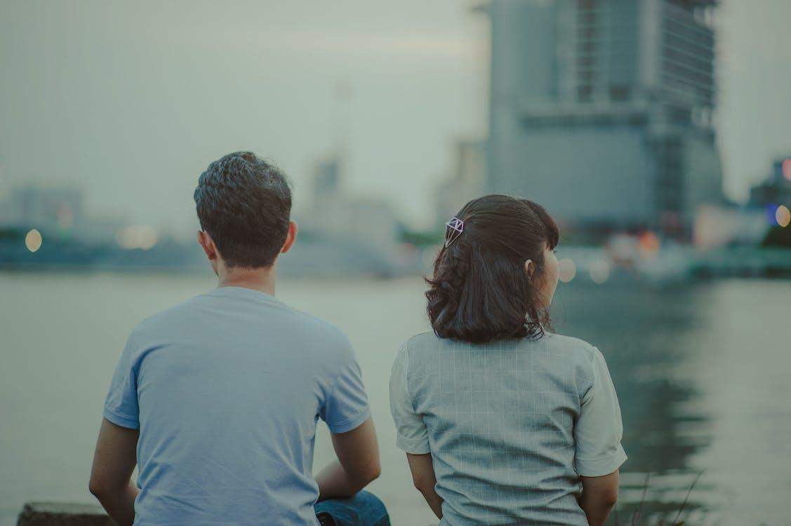 男人和女人看著水和混凝土建築物的身體選擇性聚焦攝影