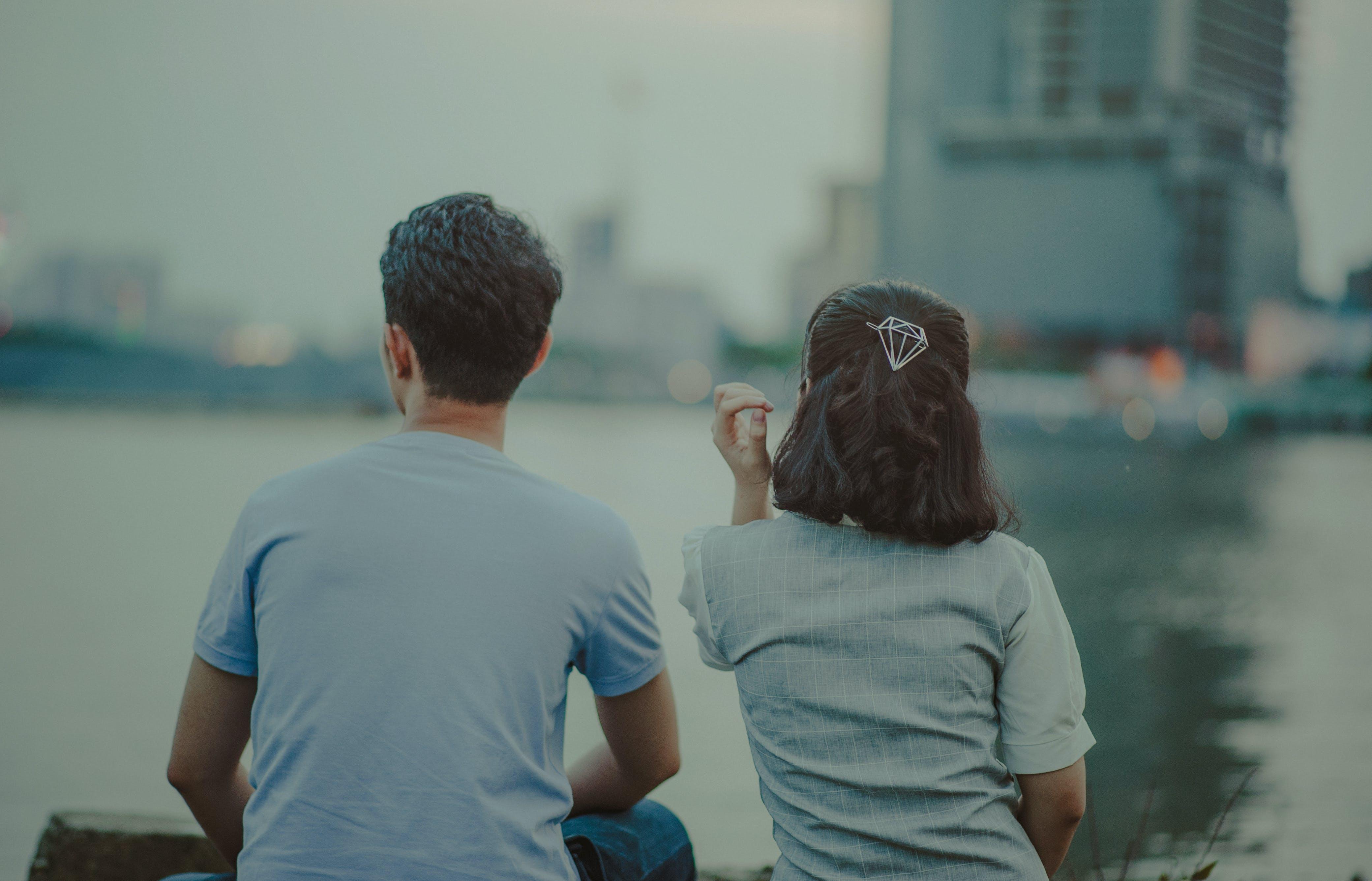 Man and Woman Wearing Shirt Facing Body of Water