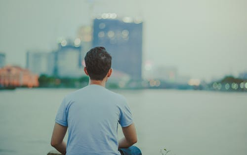 Photo of Man Wearing Blue Shirt Sitting Looking on High-rise Buildings