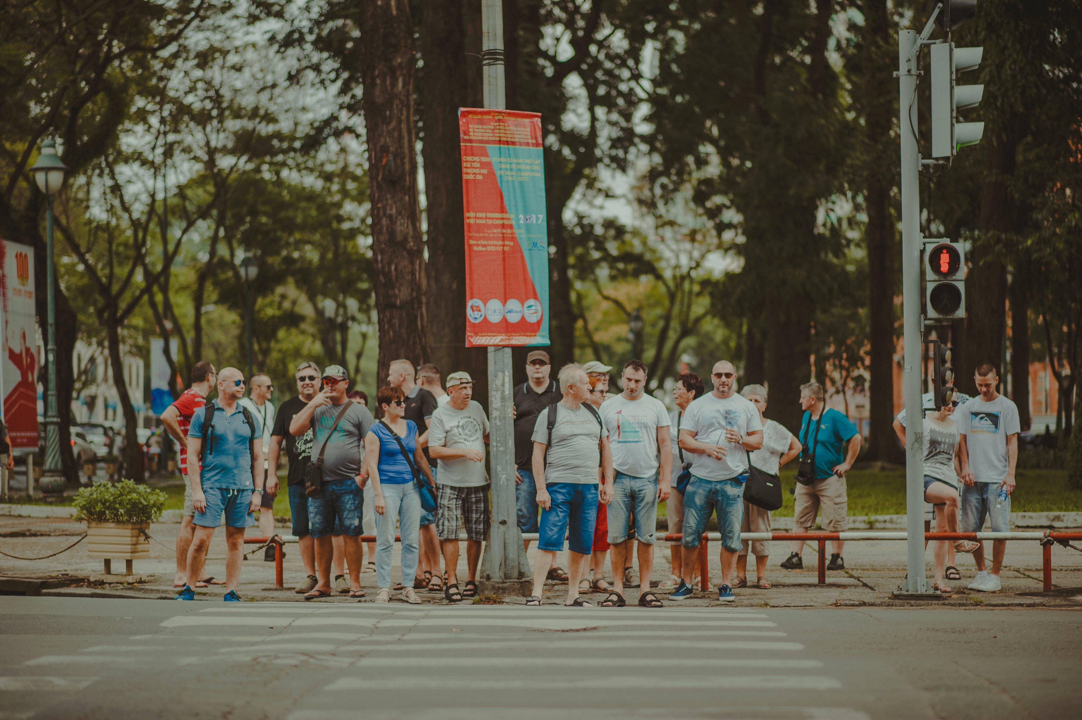 People Standing Near Metal Traffic Post