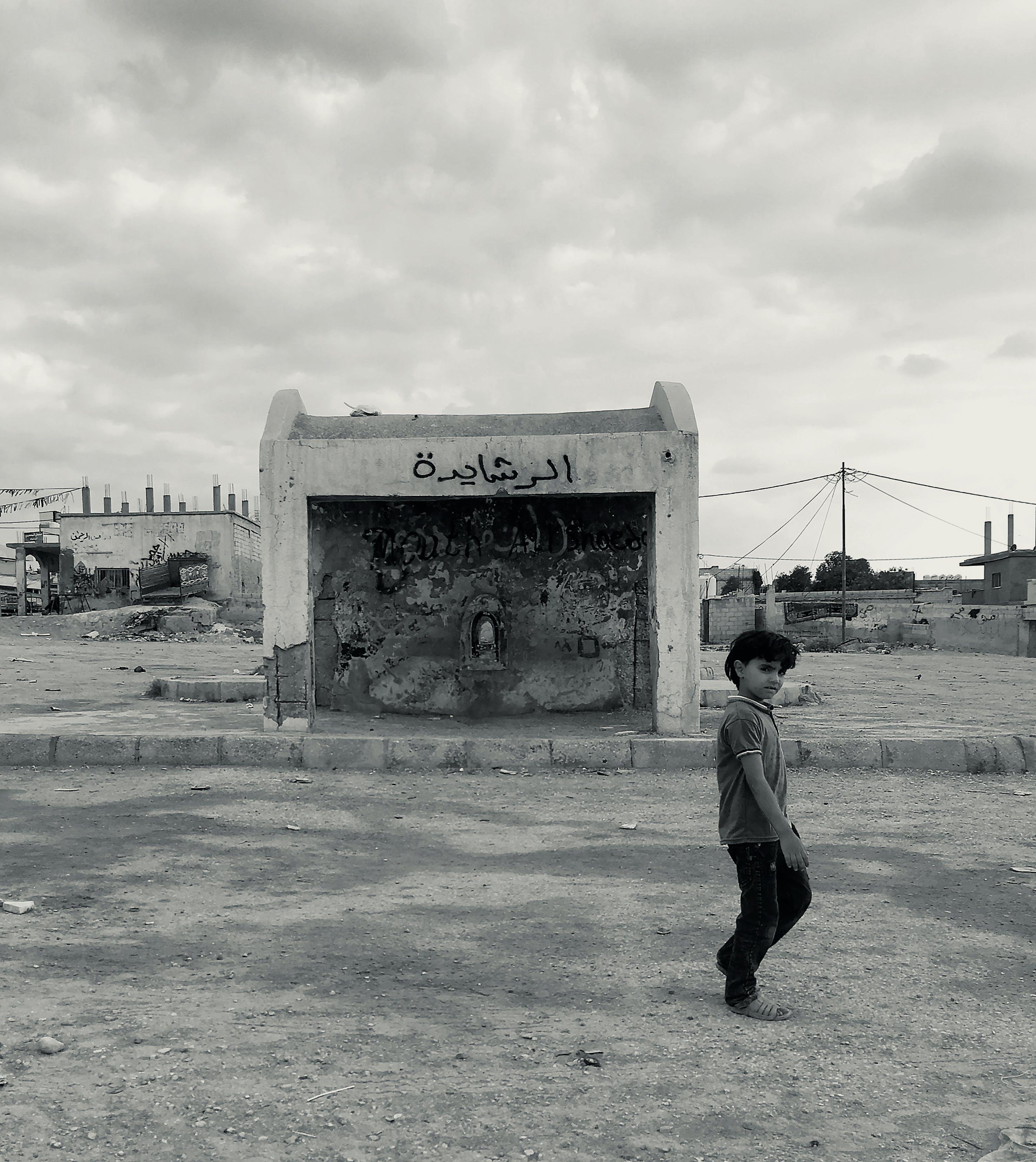 Free stock photo of black and white, boy, bus stop, run down