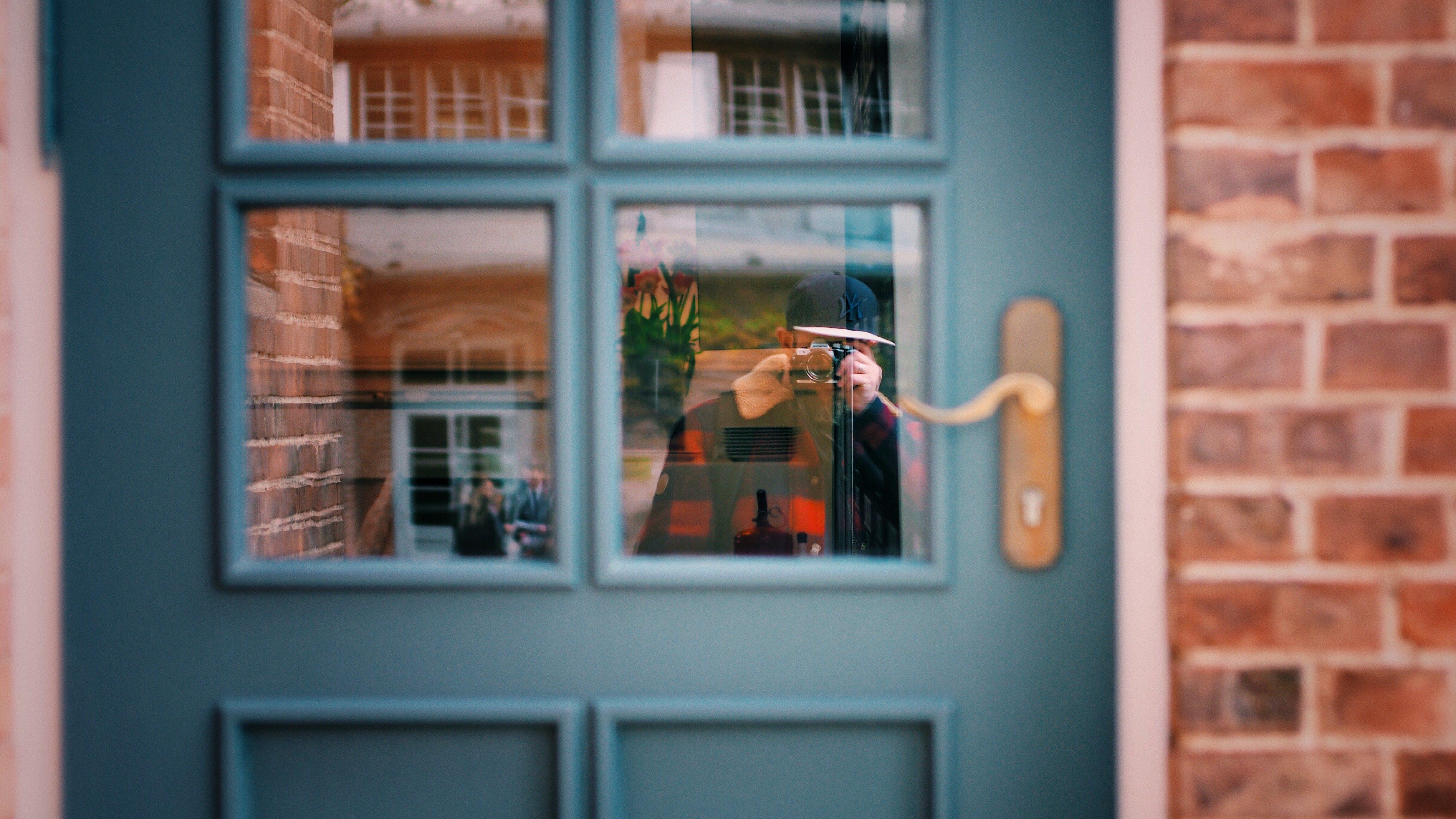 Man in Black Sweater Taking Photo of Blue Door