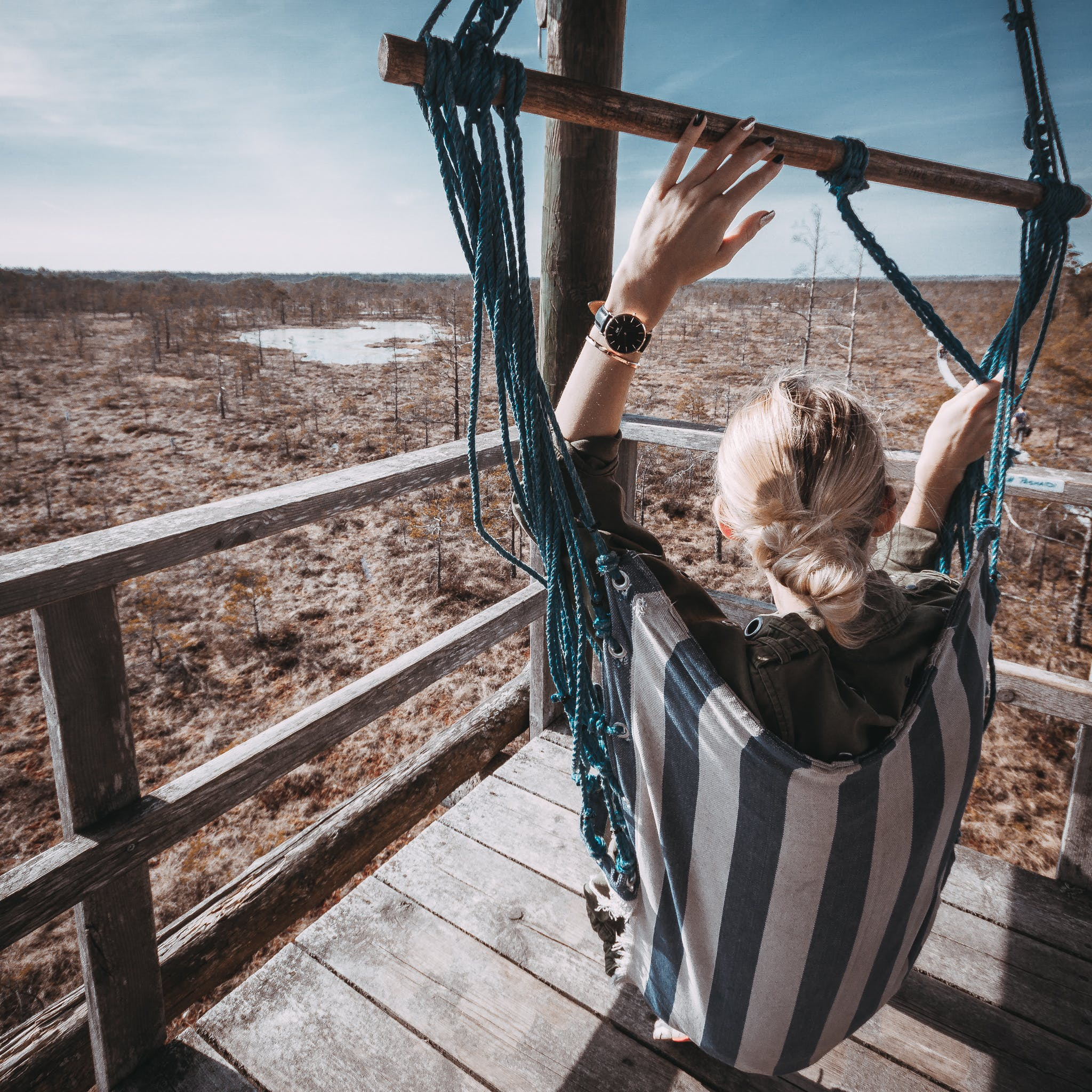 Woman With Blonde Hair On Blue And White Striped Hammock