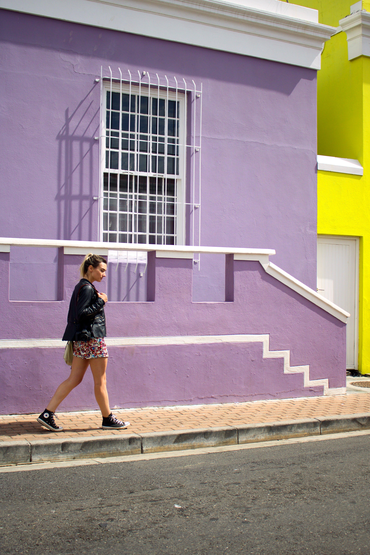 Woman Walking Near Purple Painted Building