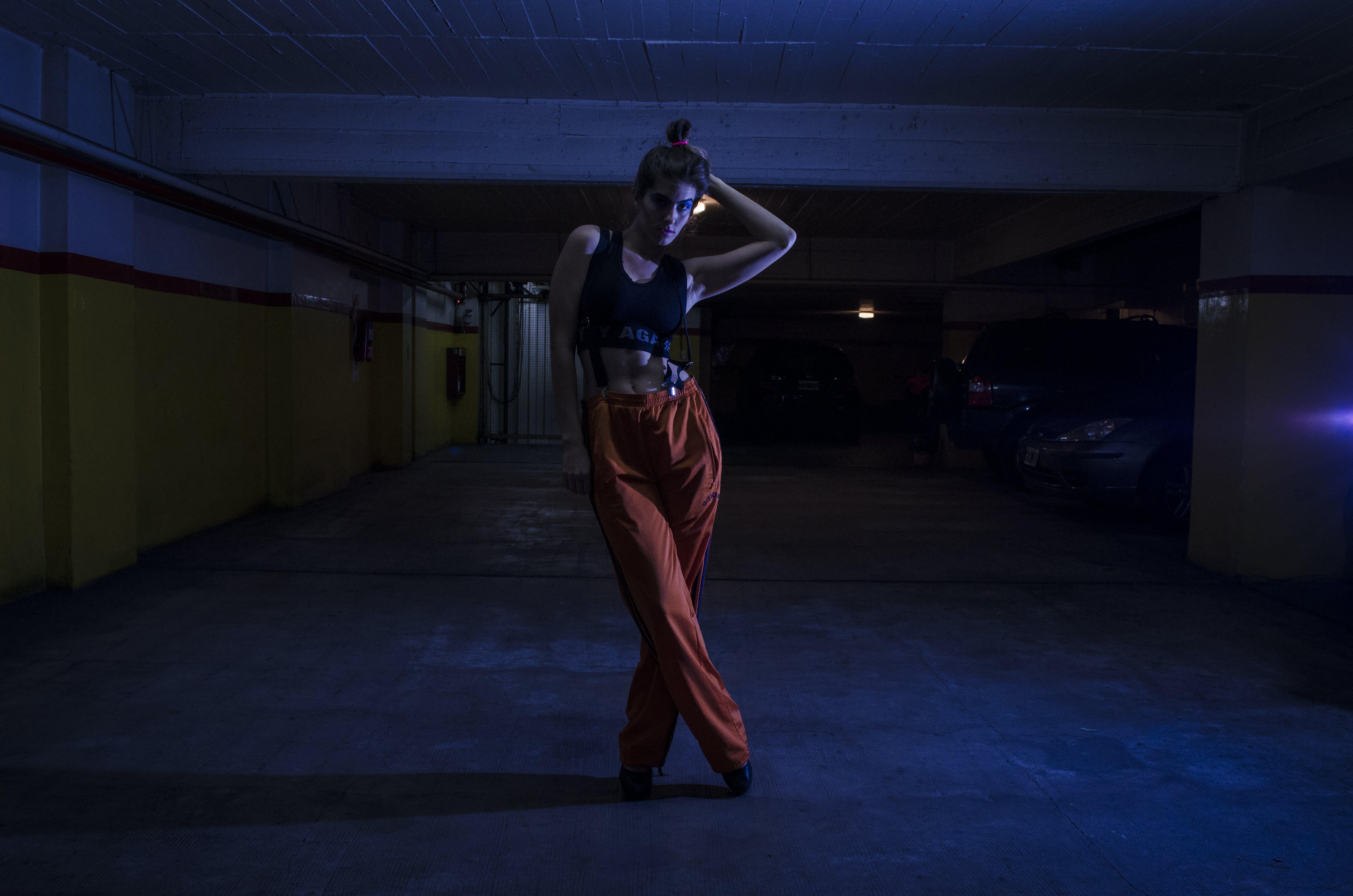 Woman Wearing Black Crop-top and Orange Pants Inside Parking Lot