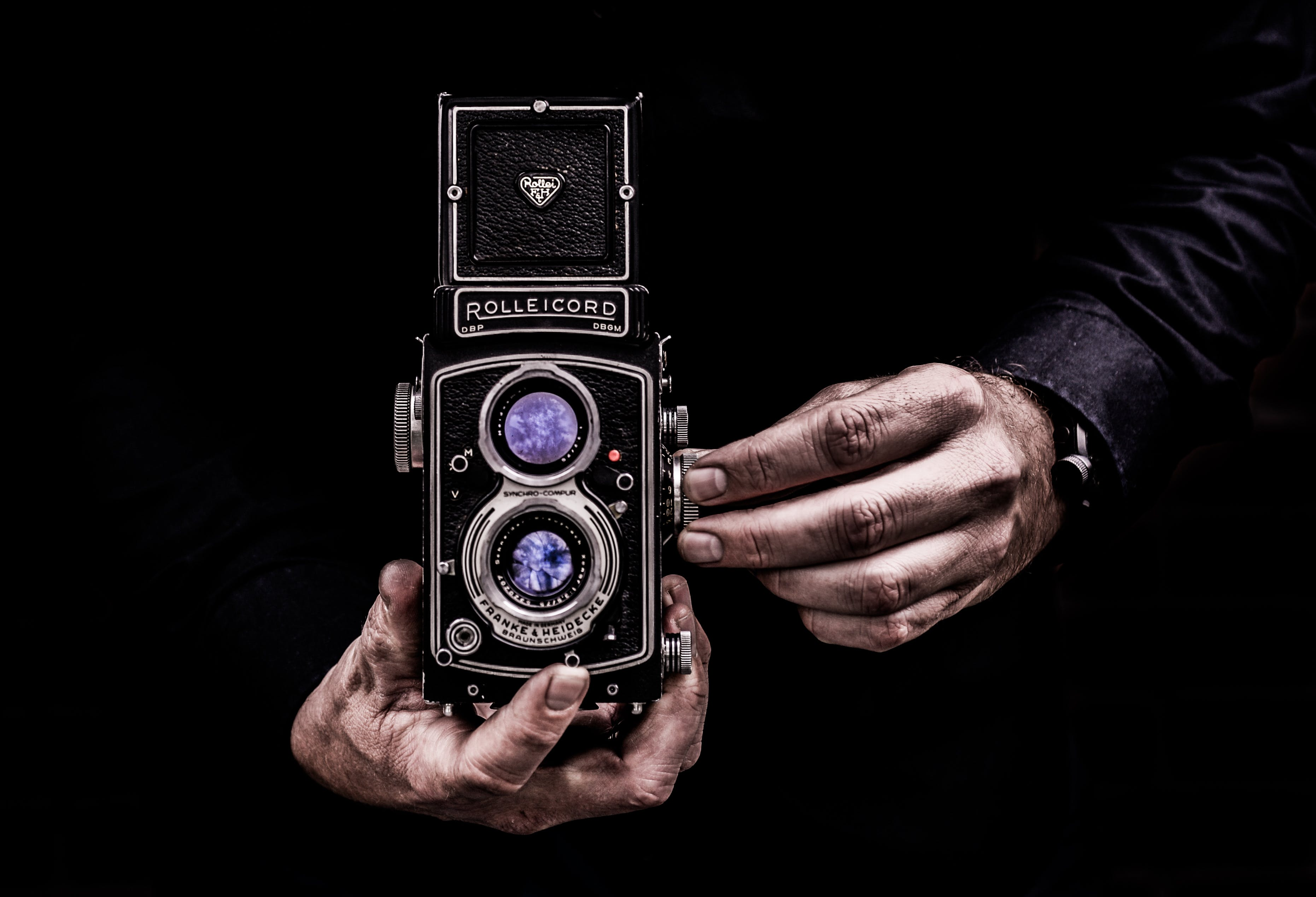 Person Holding Black Twin-lens Reflex Camera