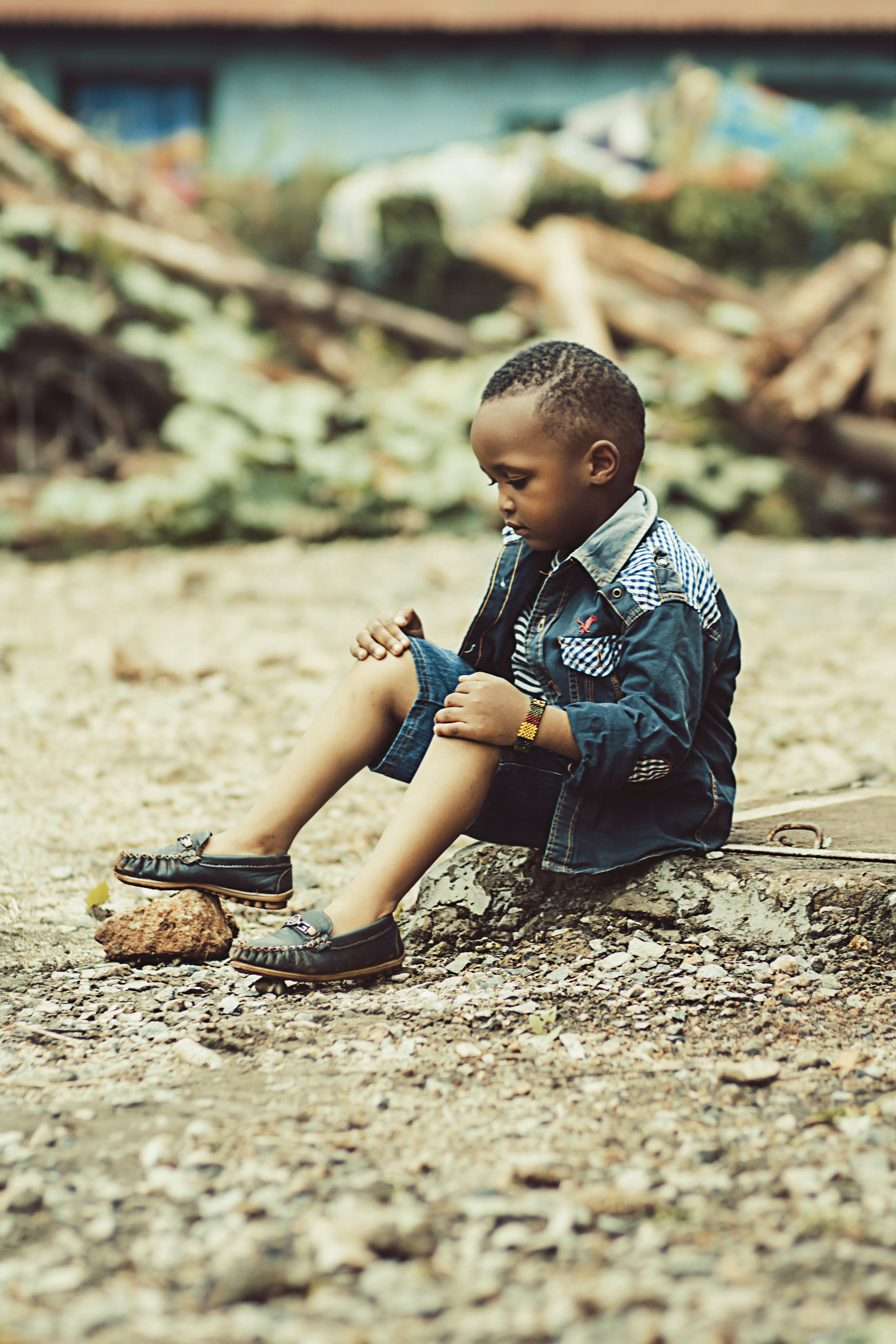 Boy Wearing Denim Jacket and Shorts With Pair of Shoes