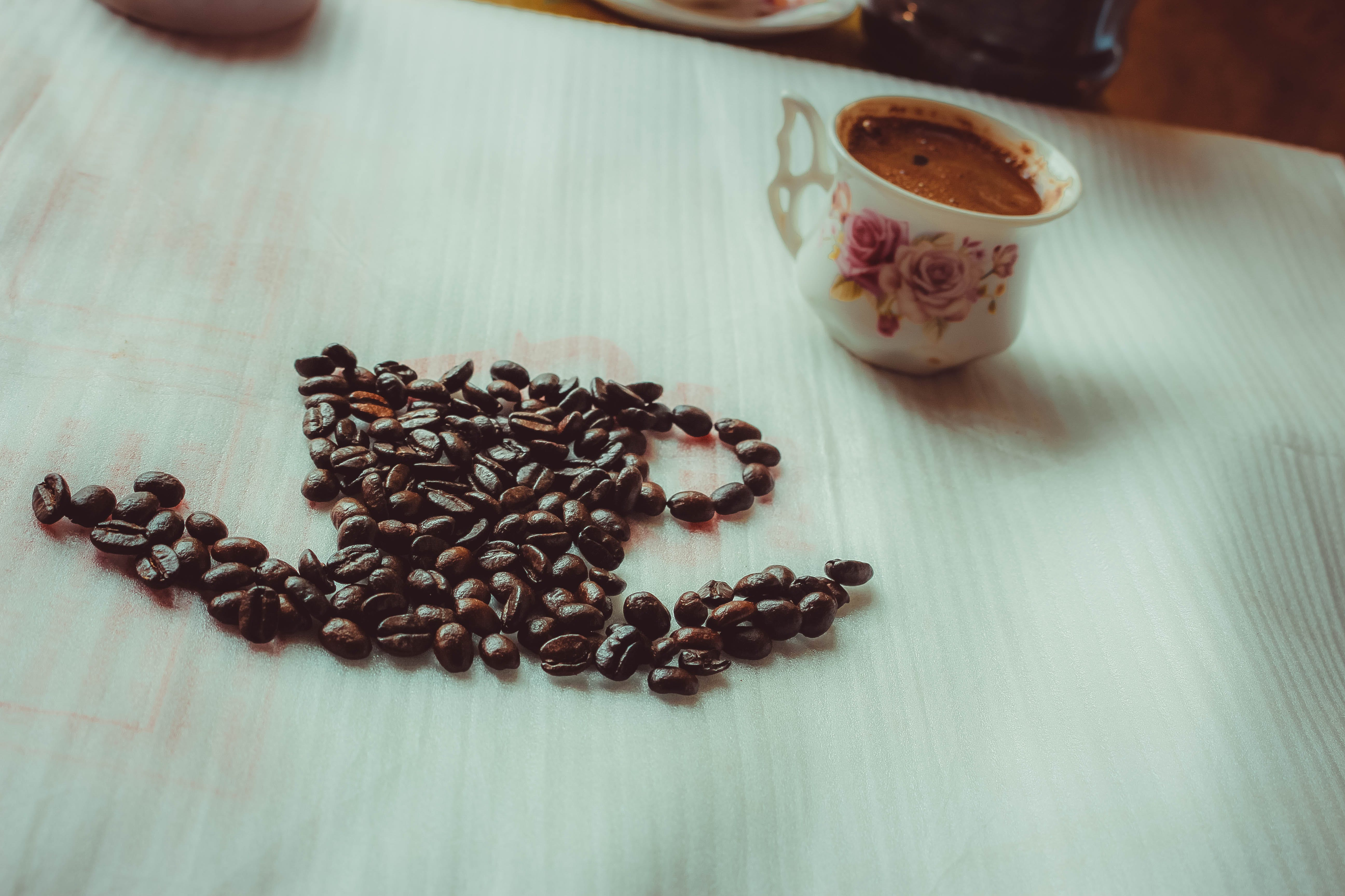 Brown Coffee Beans Beside Ceramic Mug on Table