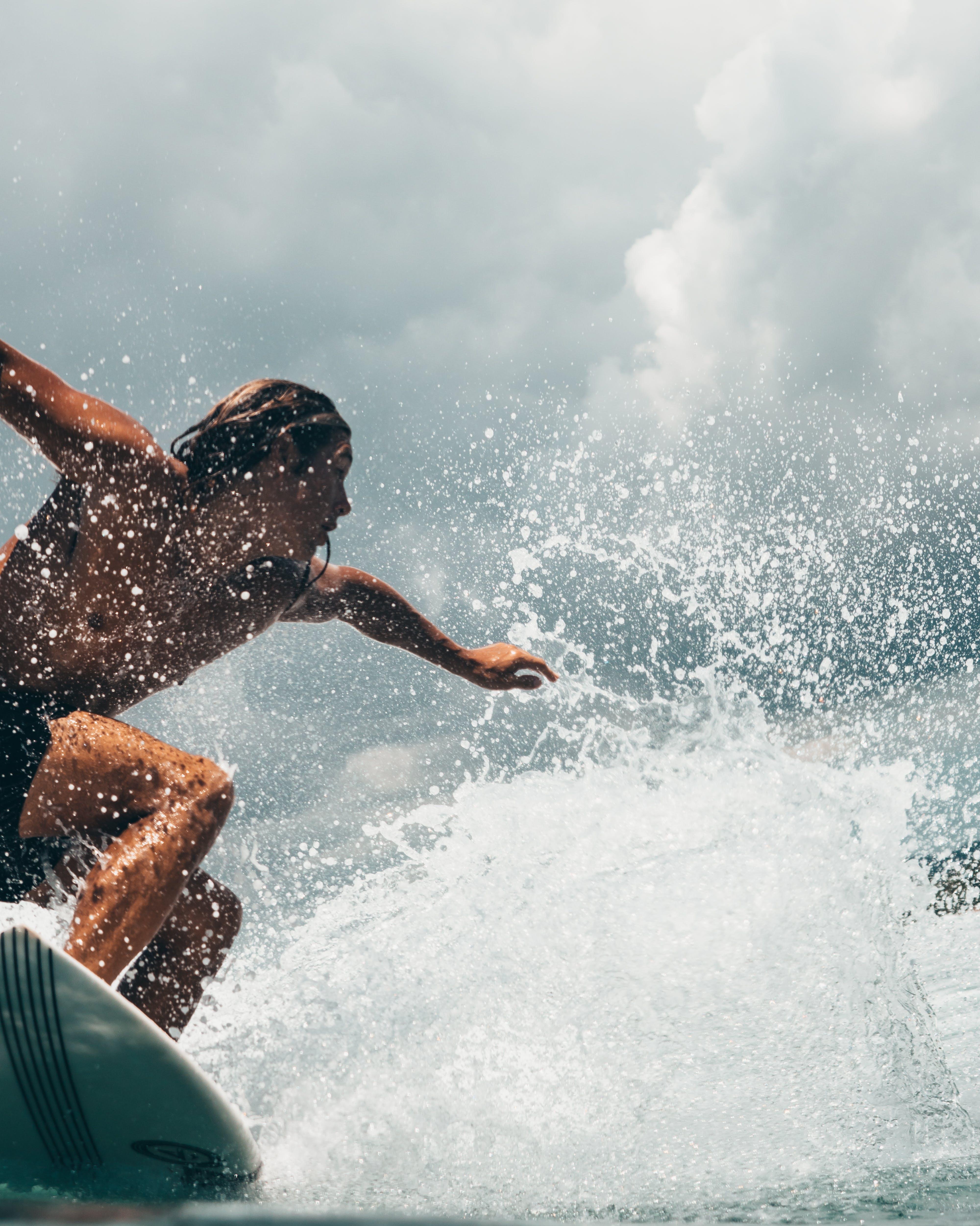 Man Riding White Surfboard