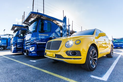 Yellow Vehicle Parked Beside Blue Truck