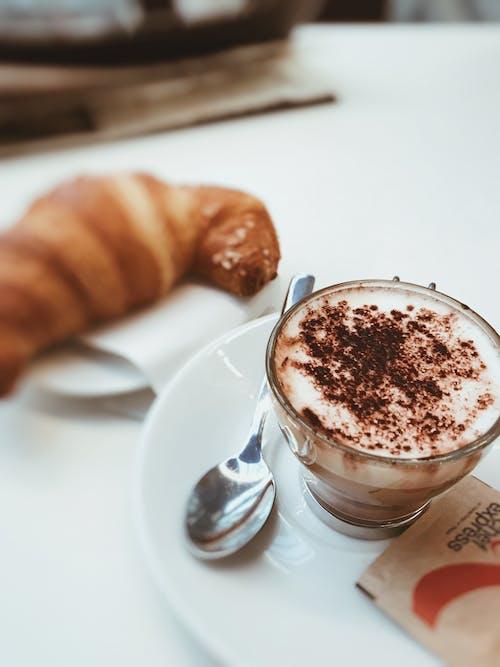 Фотография чашки, наполненной кофе, на белом керамическом блюдце в выборочном фокусе