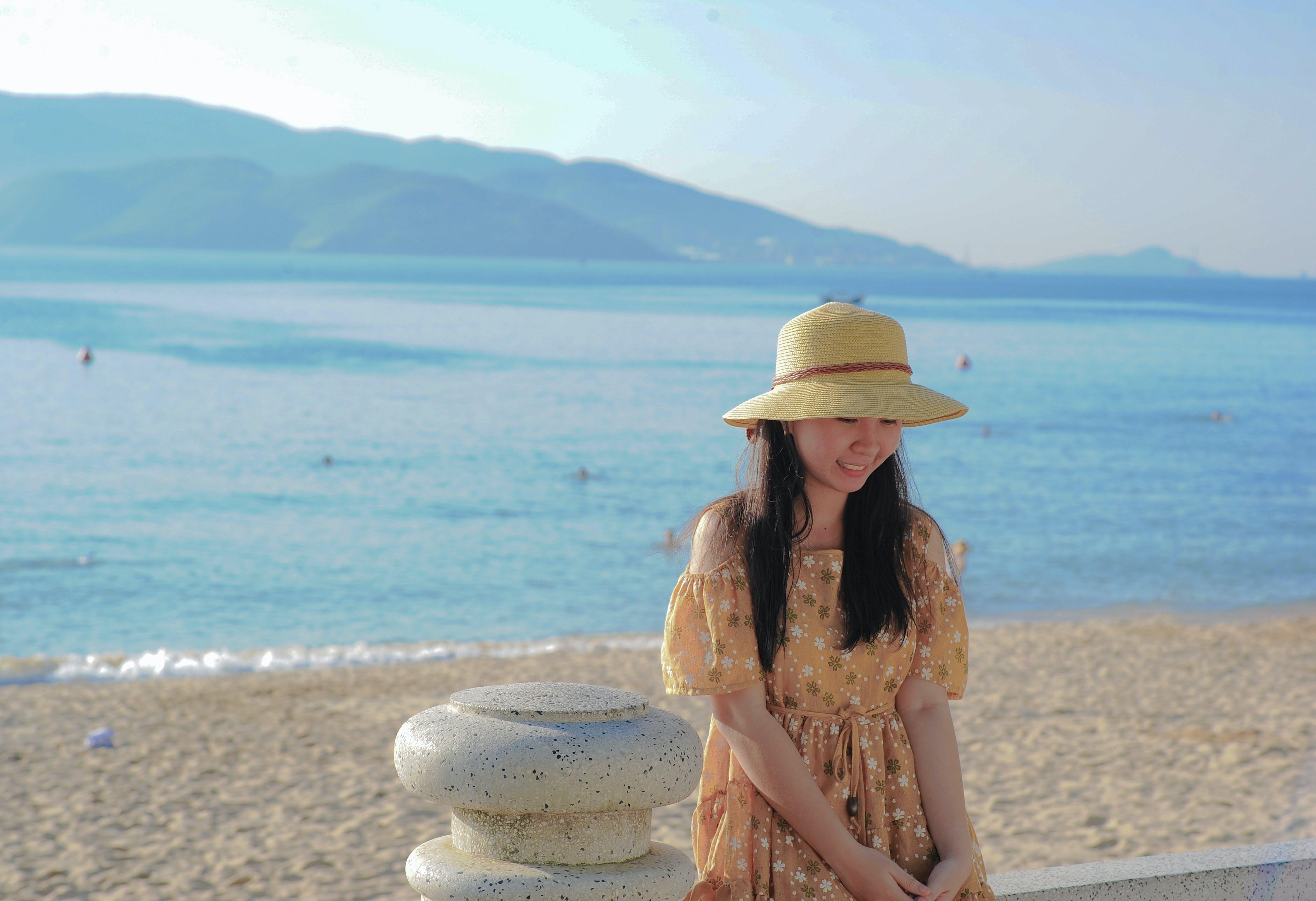 Woman Wearing Brown Off-shoulder Dress Near Ocean Water