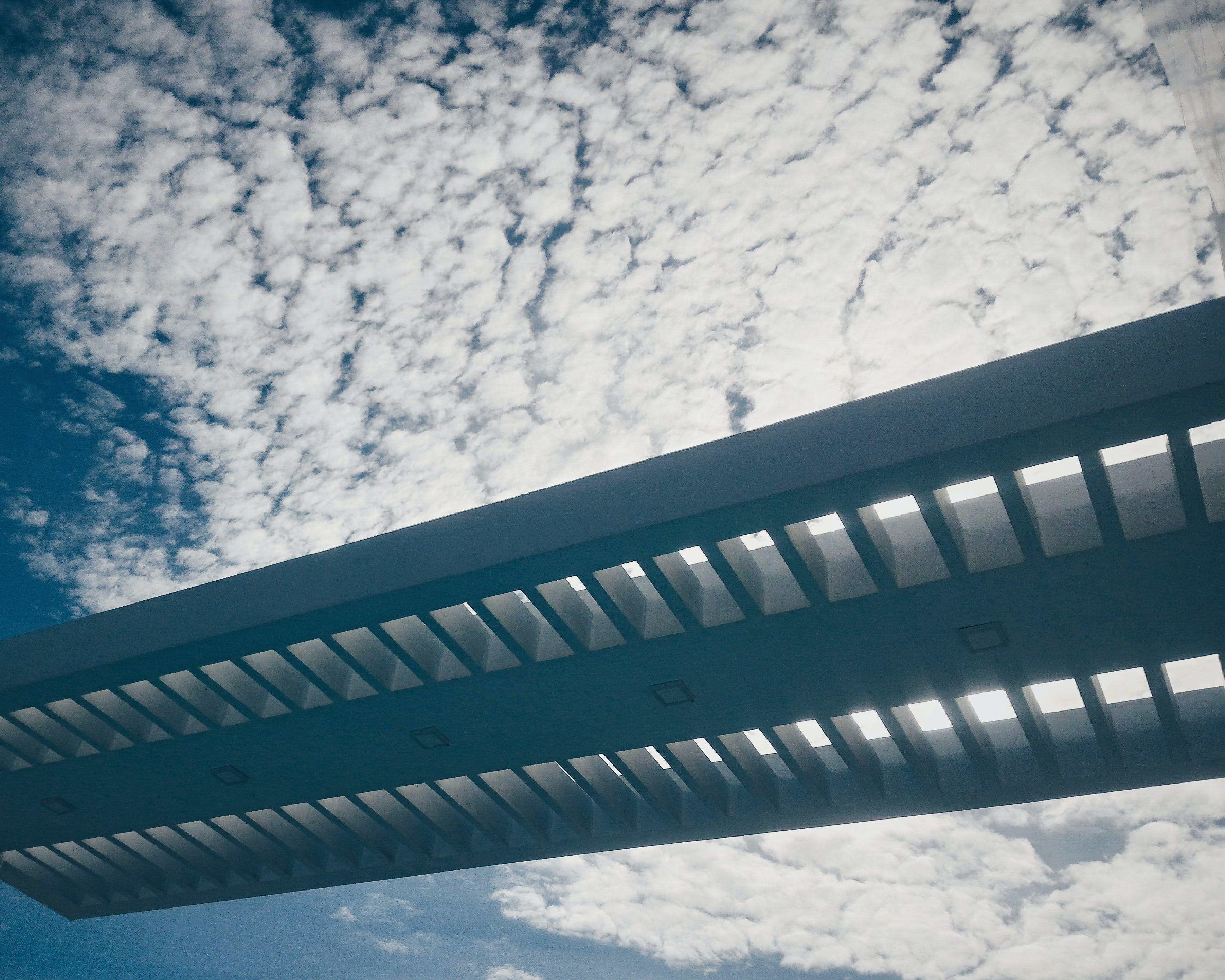 Silhouette of Bridge Under Cloudy Sky