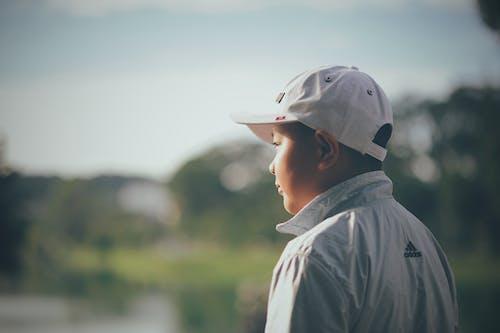 Kid Wearing White Cap and Adidas Jacket
