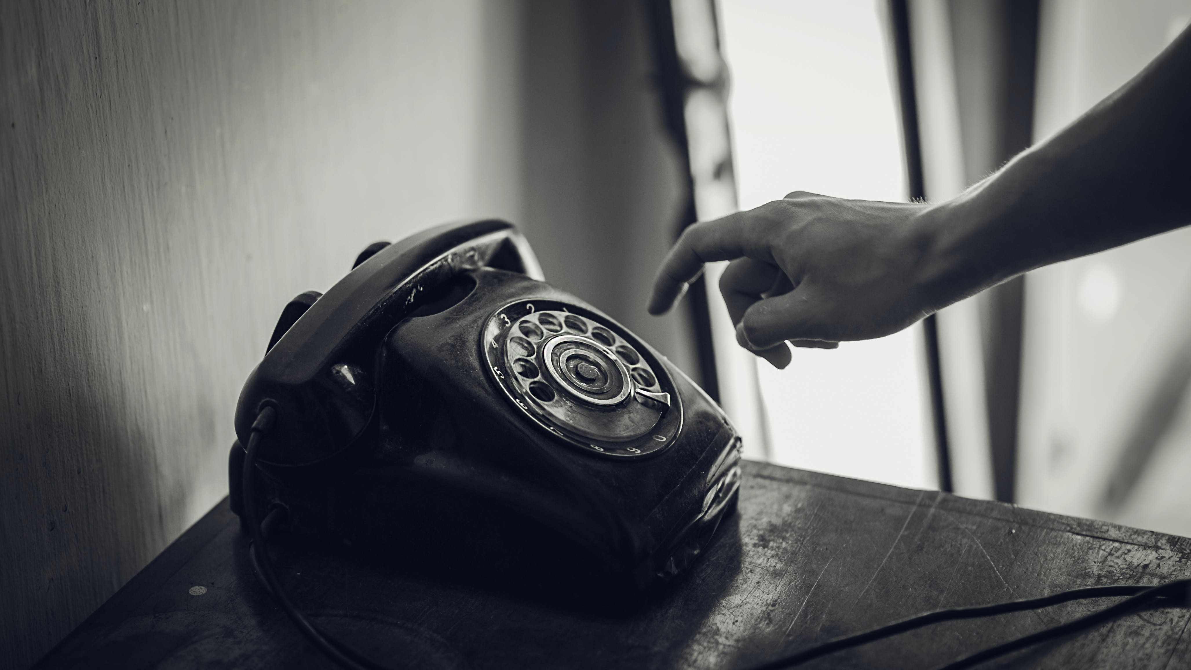 Grayscale Photo of Rotary Telephone Beside Person Hand