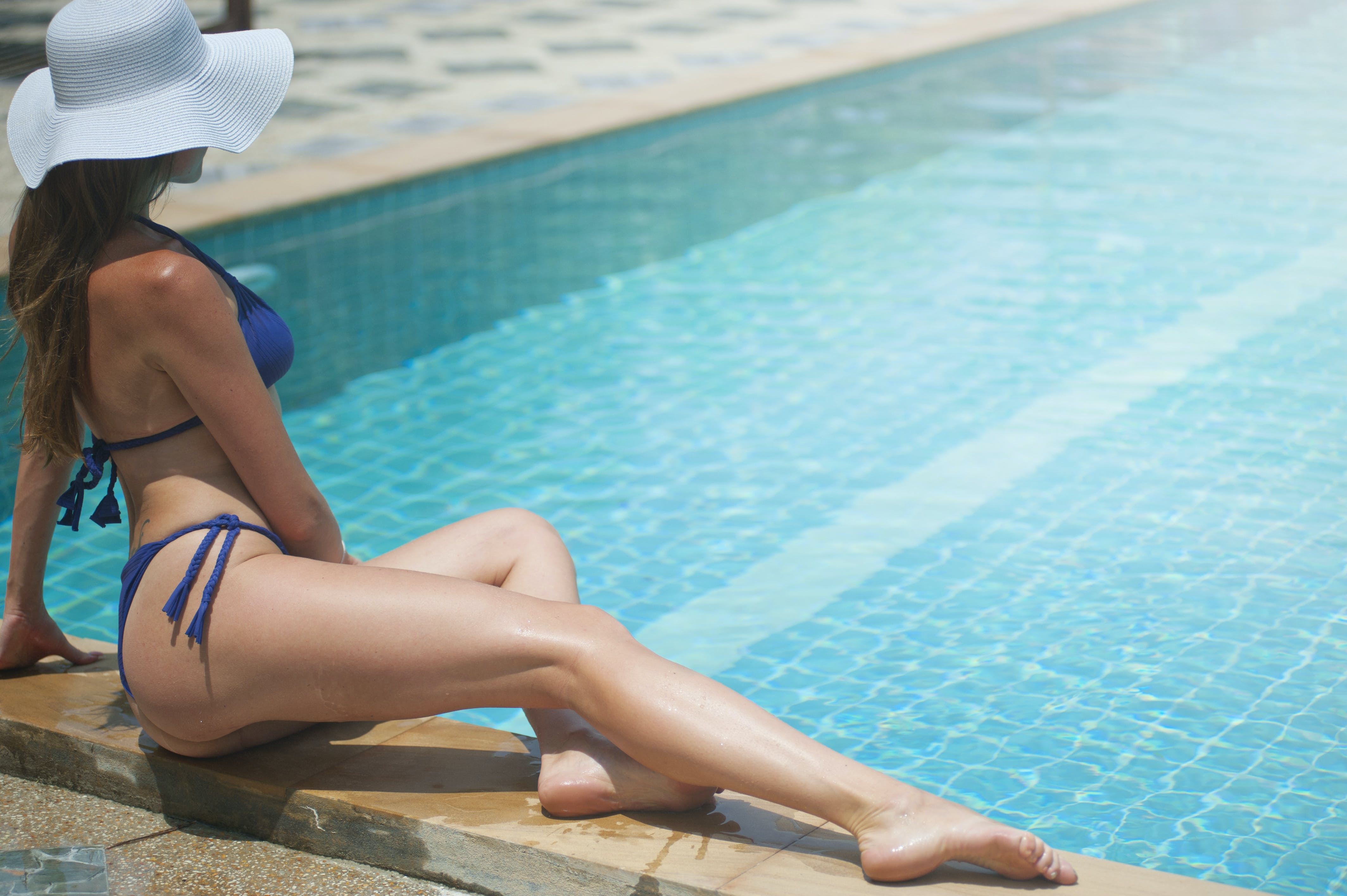 Woman Wearing Blue Bikini Set Sitting Beside Pool