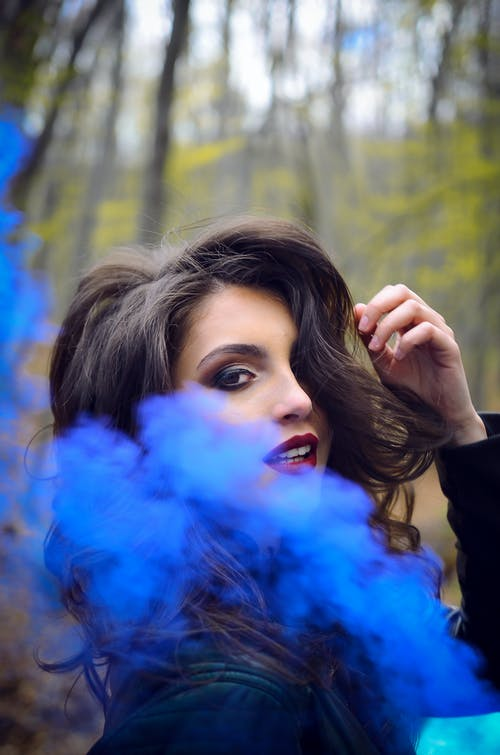 Close-Up Photography of a Woman Near Blue Smoke