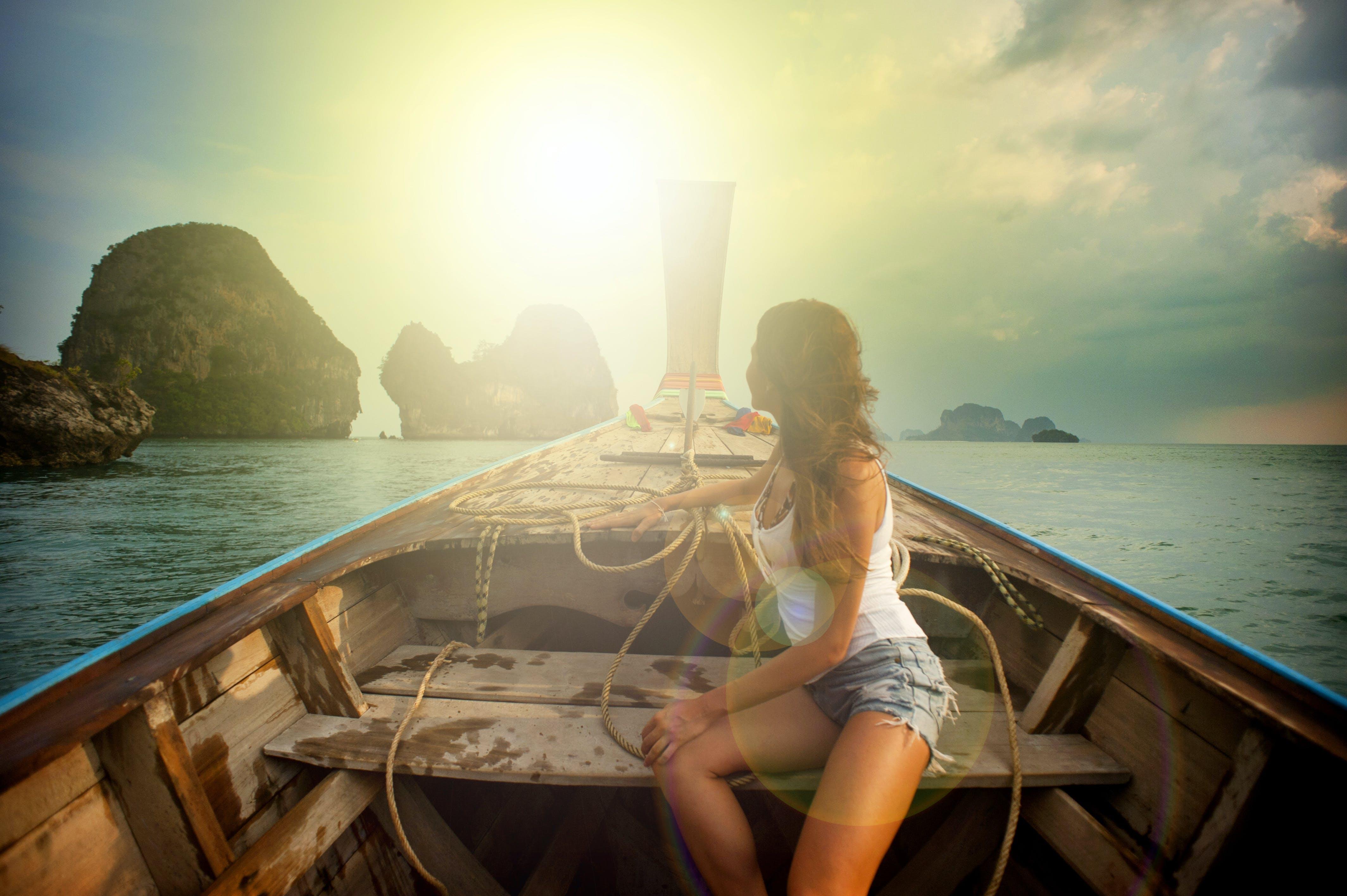Woman Wearing White Tank Top Seating on Boat