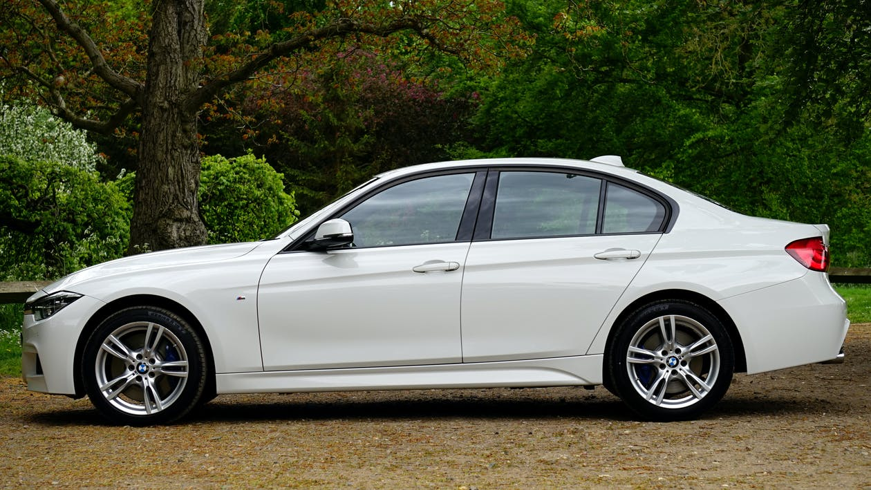 White Bmw Sedan Parked Beside Tree