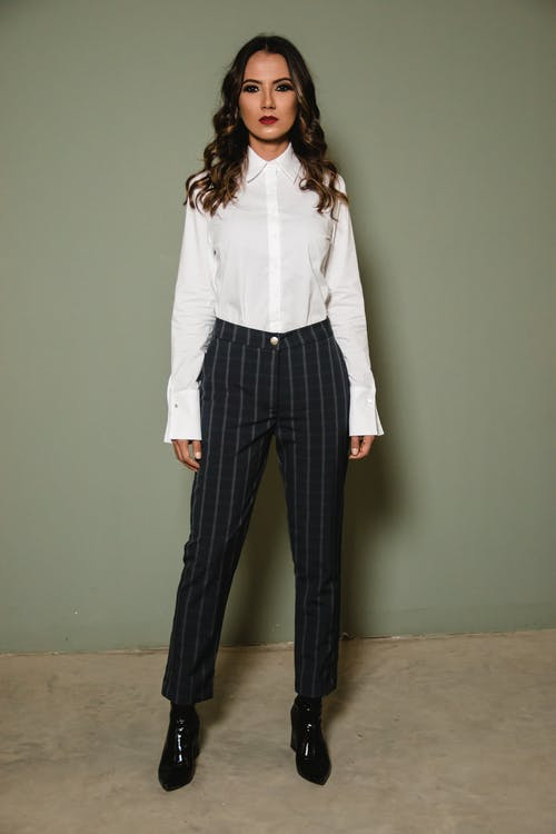 Woman Posing in White Dress Shirt and Black Pants Standing Against Gray Wall