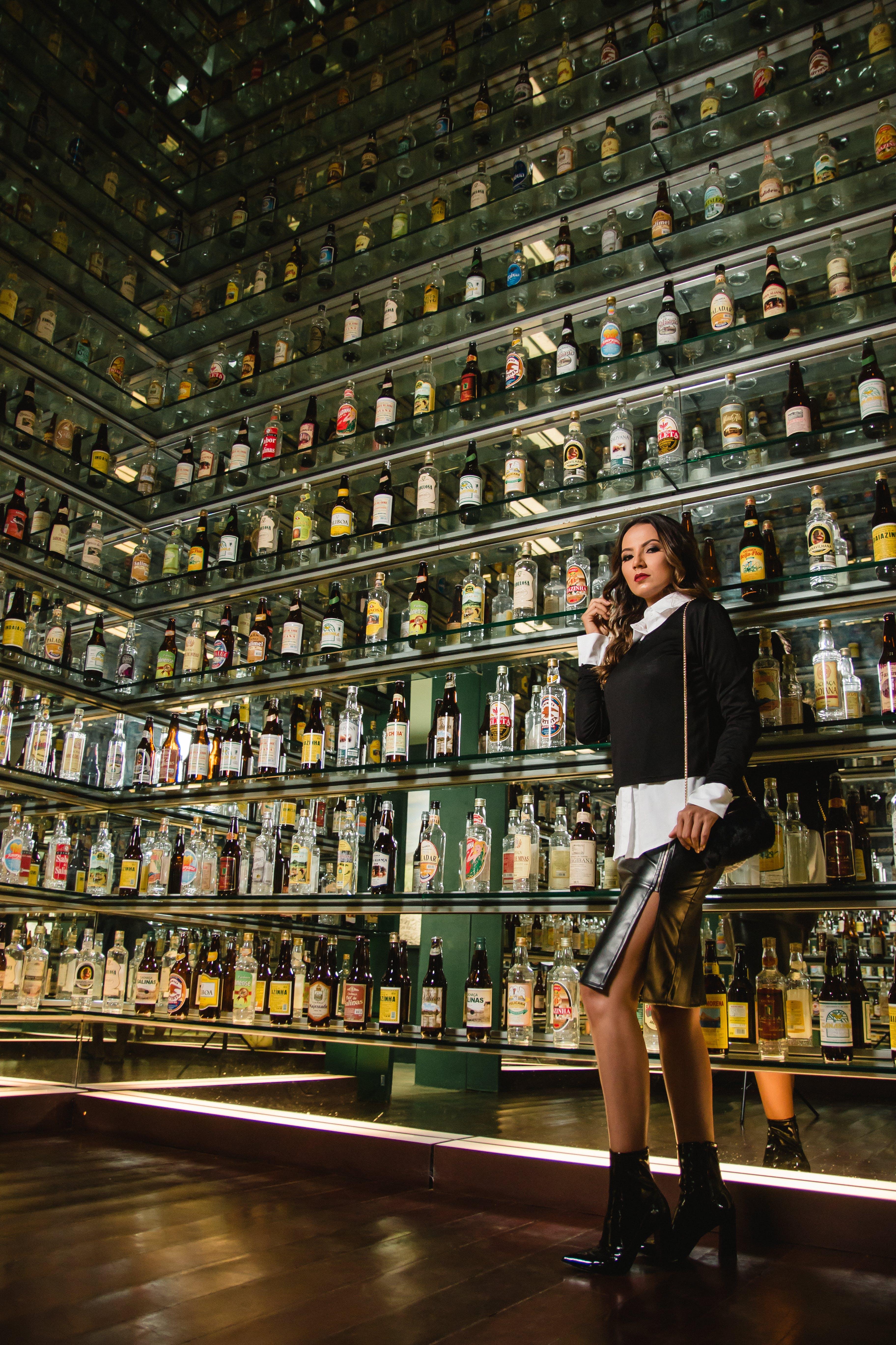 Photo of Woman Standing Near Shelves for Liquor