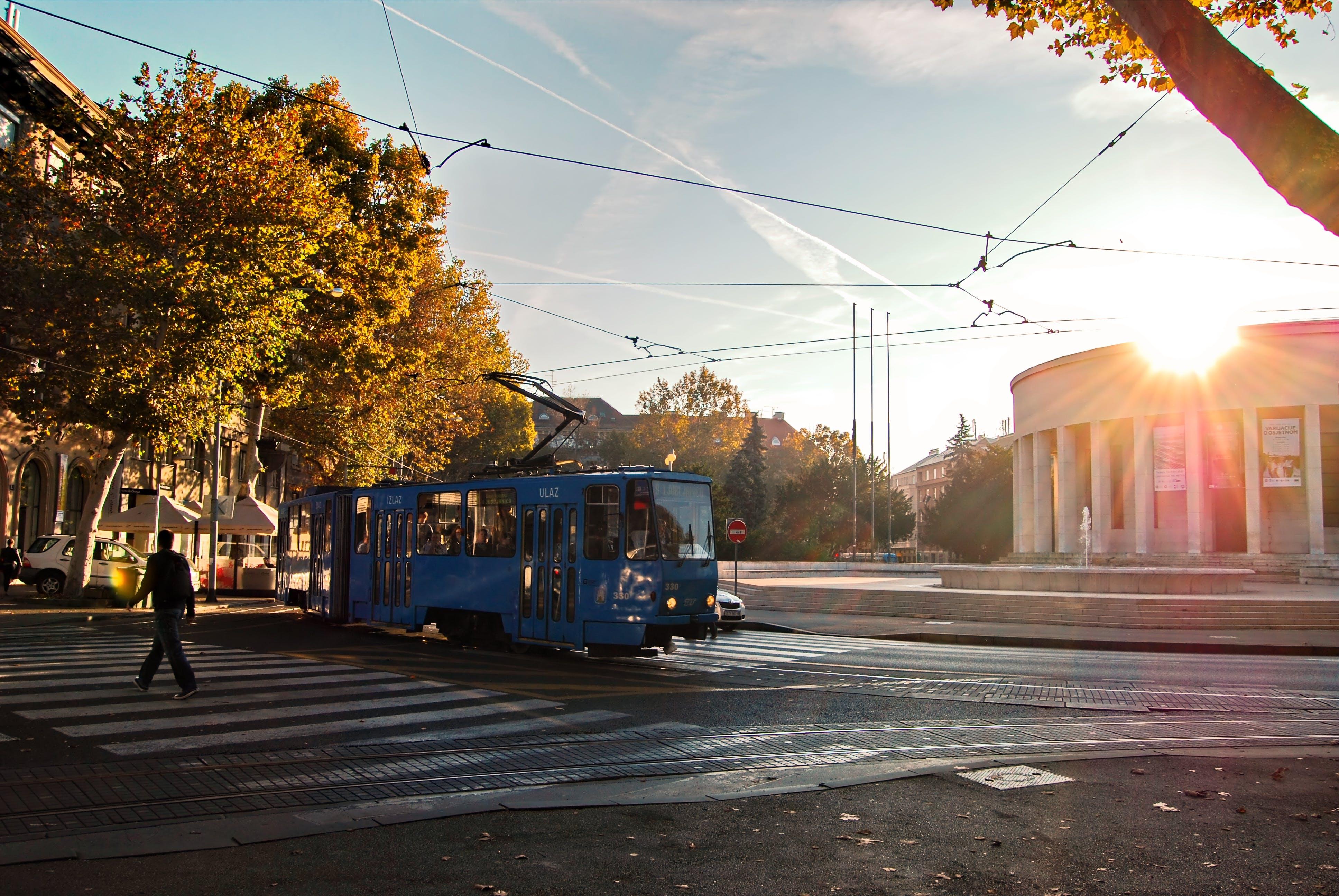 Person Wearing Black Walking on Pedestrian Lane Near Blue Tram Train during Sunset