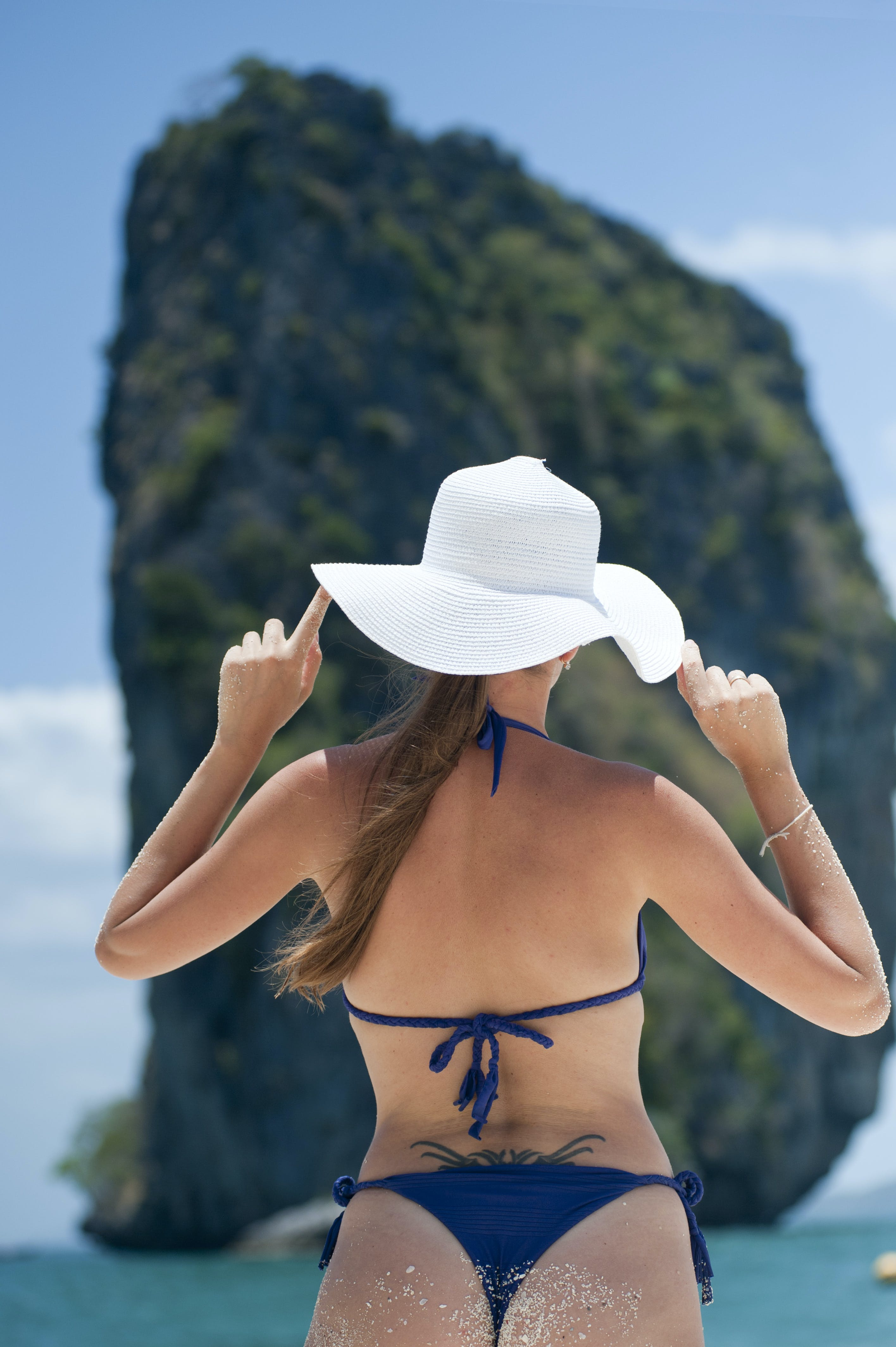 Woman In Blue Bikini Set Wearing White Sun Hat In Front Of Rock Formation