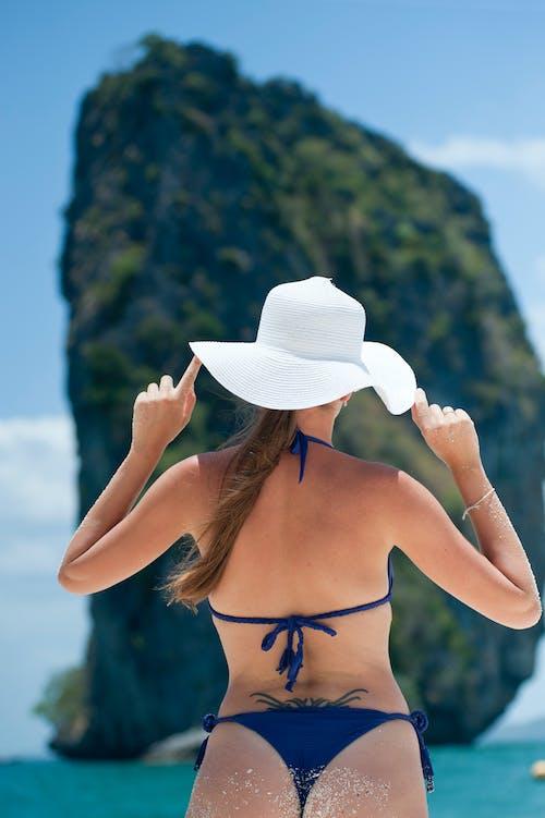 Woman In Blue Bikini Set Wearing White Sun Hat In Front Of Rock Formation