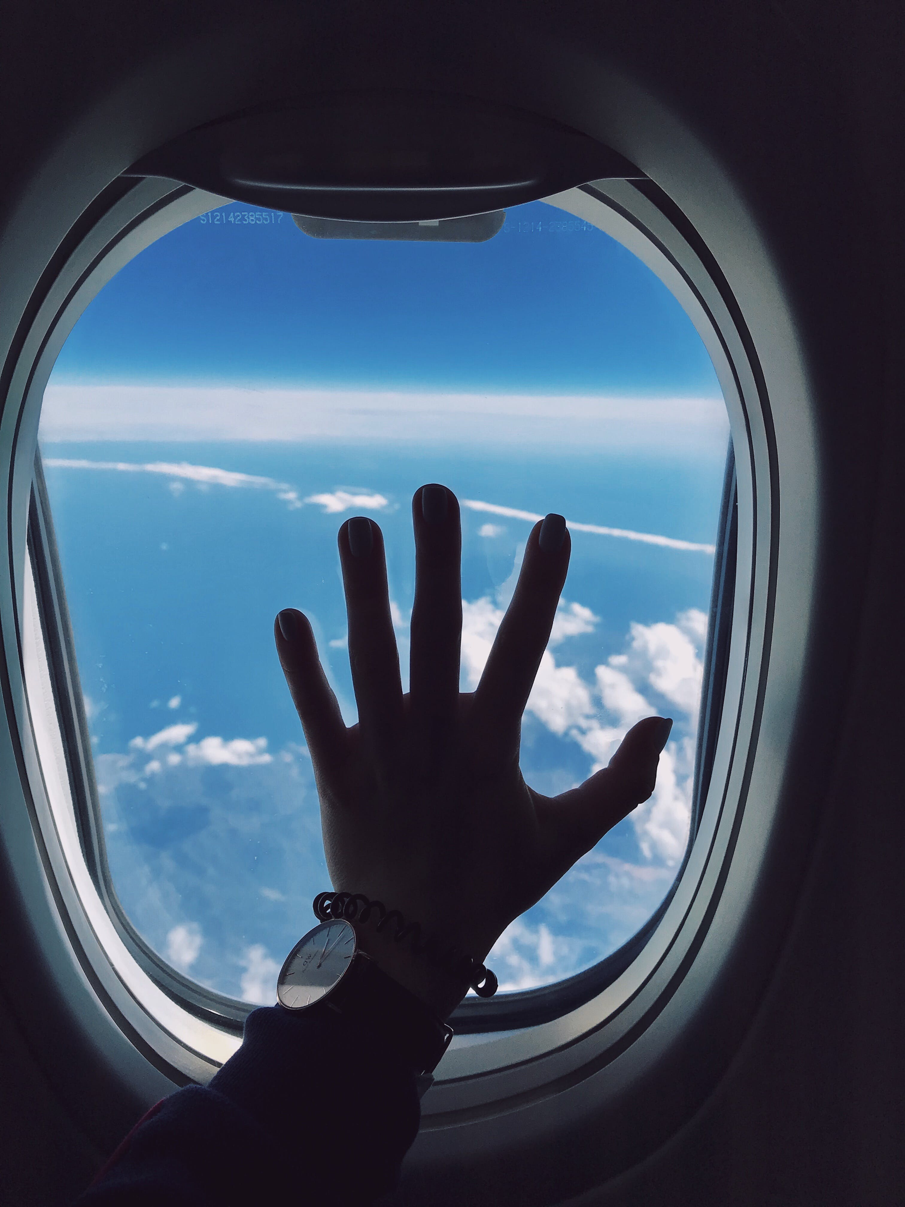 Photography of Person's Left Hand Touching an Airplane's Window