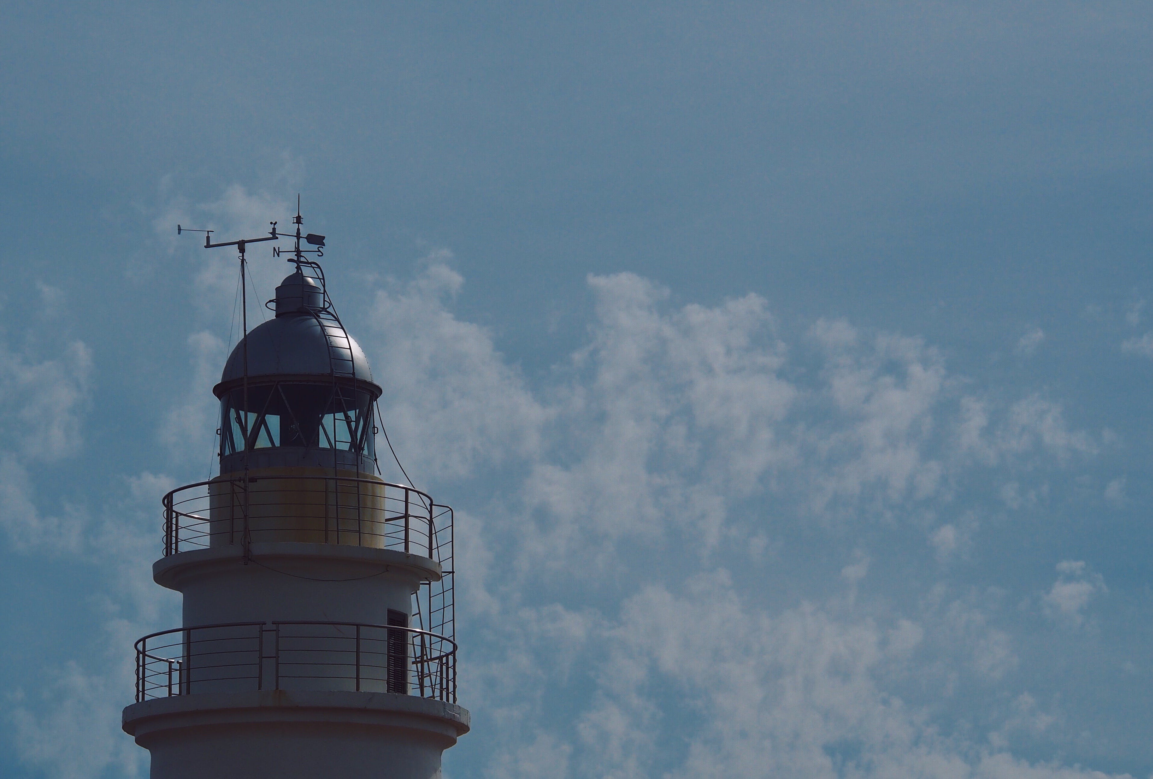 White Lighthouse Under Blue Sky and White Clouds