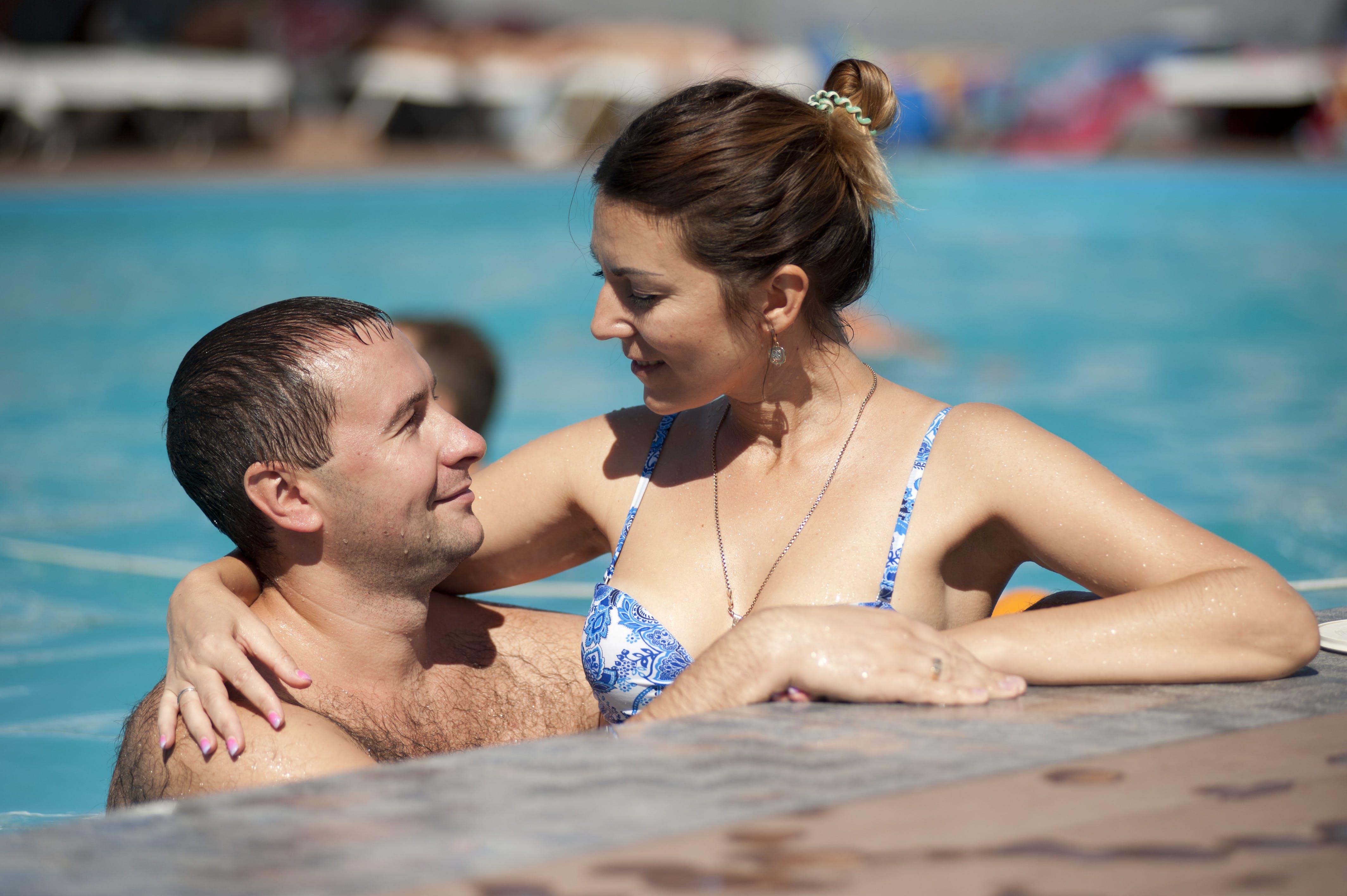 Woman in Blue Bikini Top Hugging Topless Man