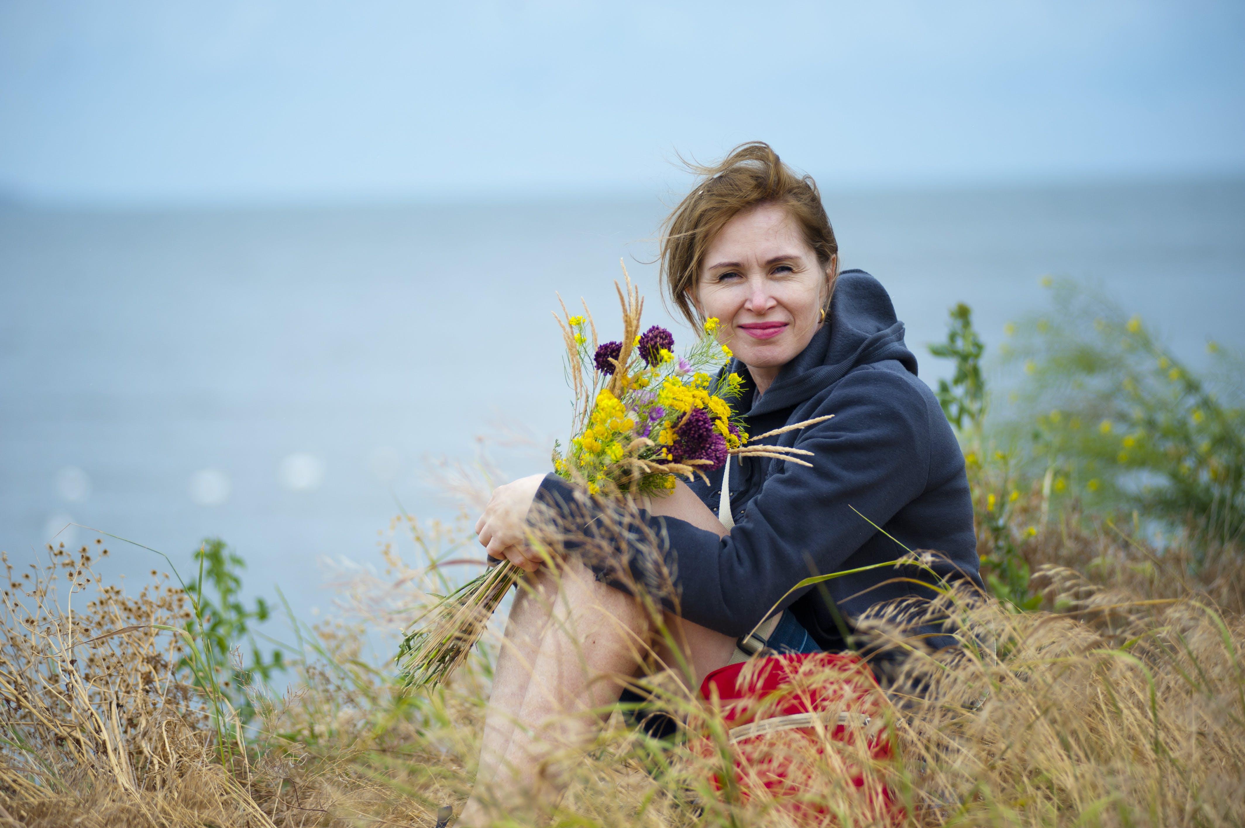 Woman Sitting on Grass Holding Flowers Wearing Black Hoodie