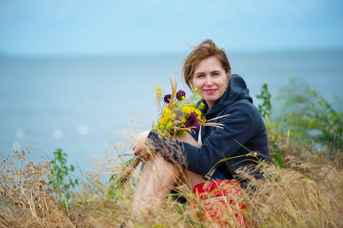 Woman Sitting on Grass Holding Flowers Wearing Black Hoodie