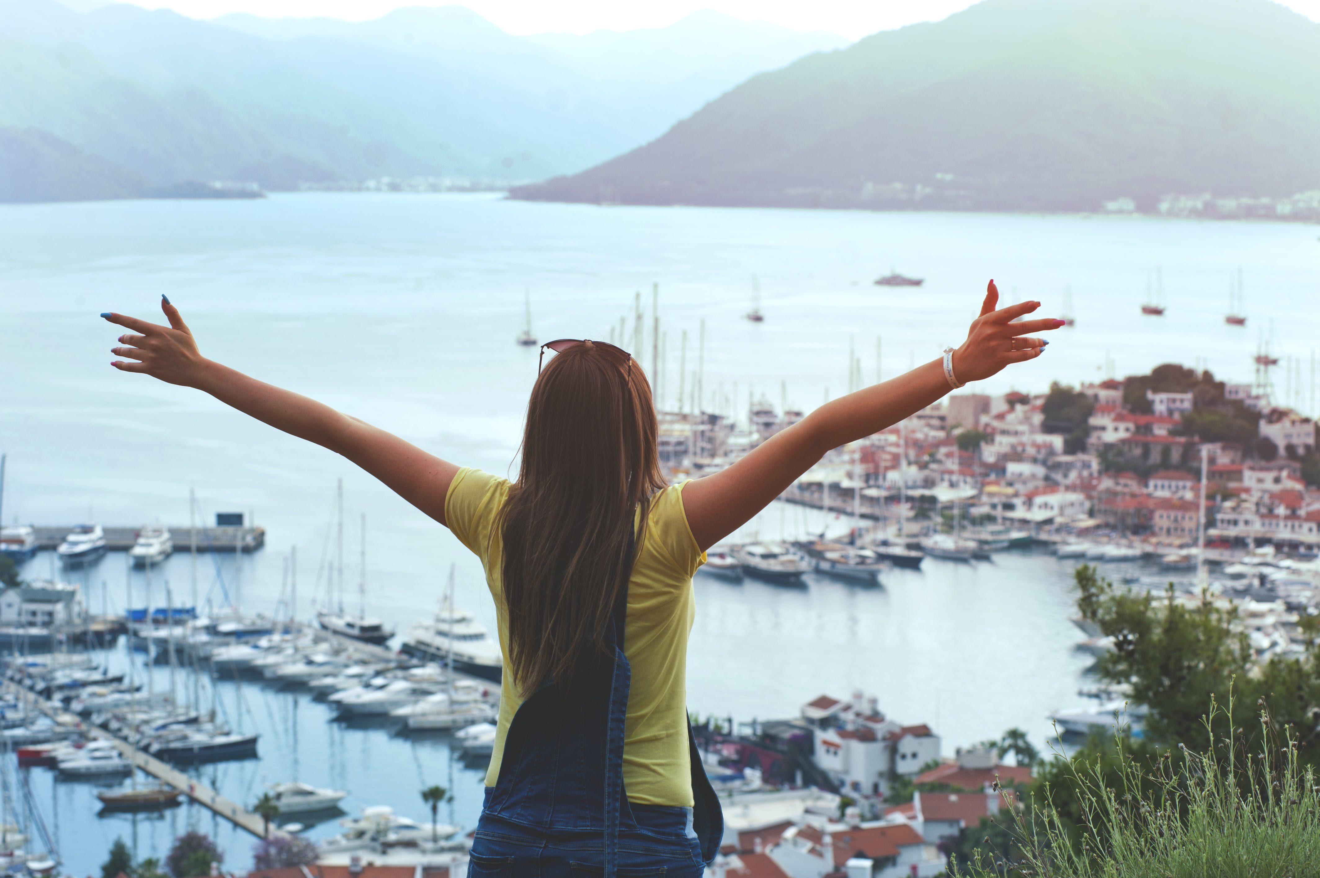 Woman Raising Her Hands Facing Cityscape Near Body of Water