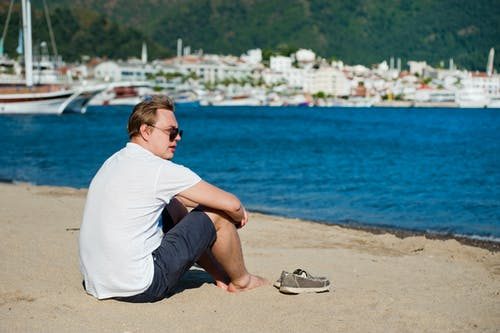 Photo of Man in White Shirt and Blue Short Sitting on Seashore