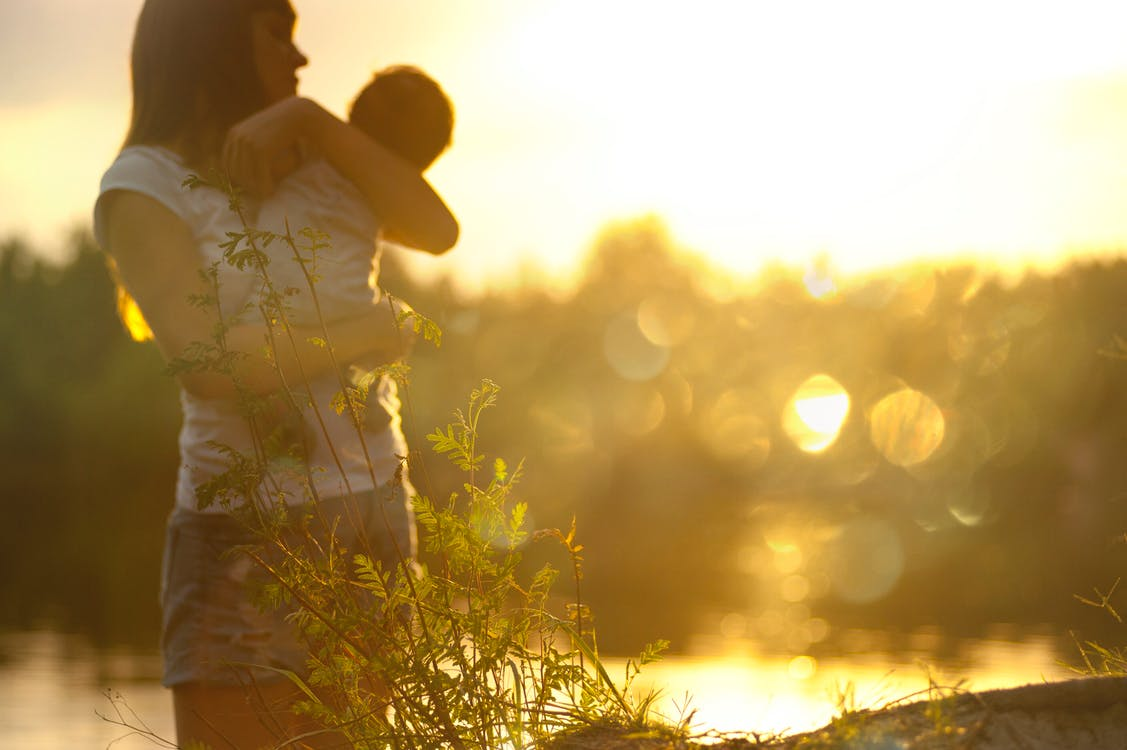 Selective Focus Photography of Woman Carrying Baby
