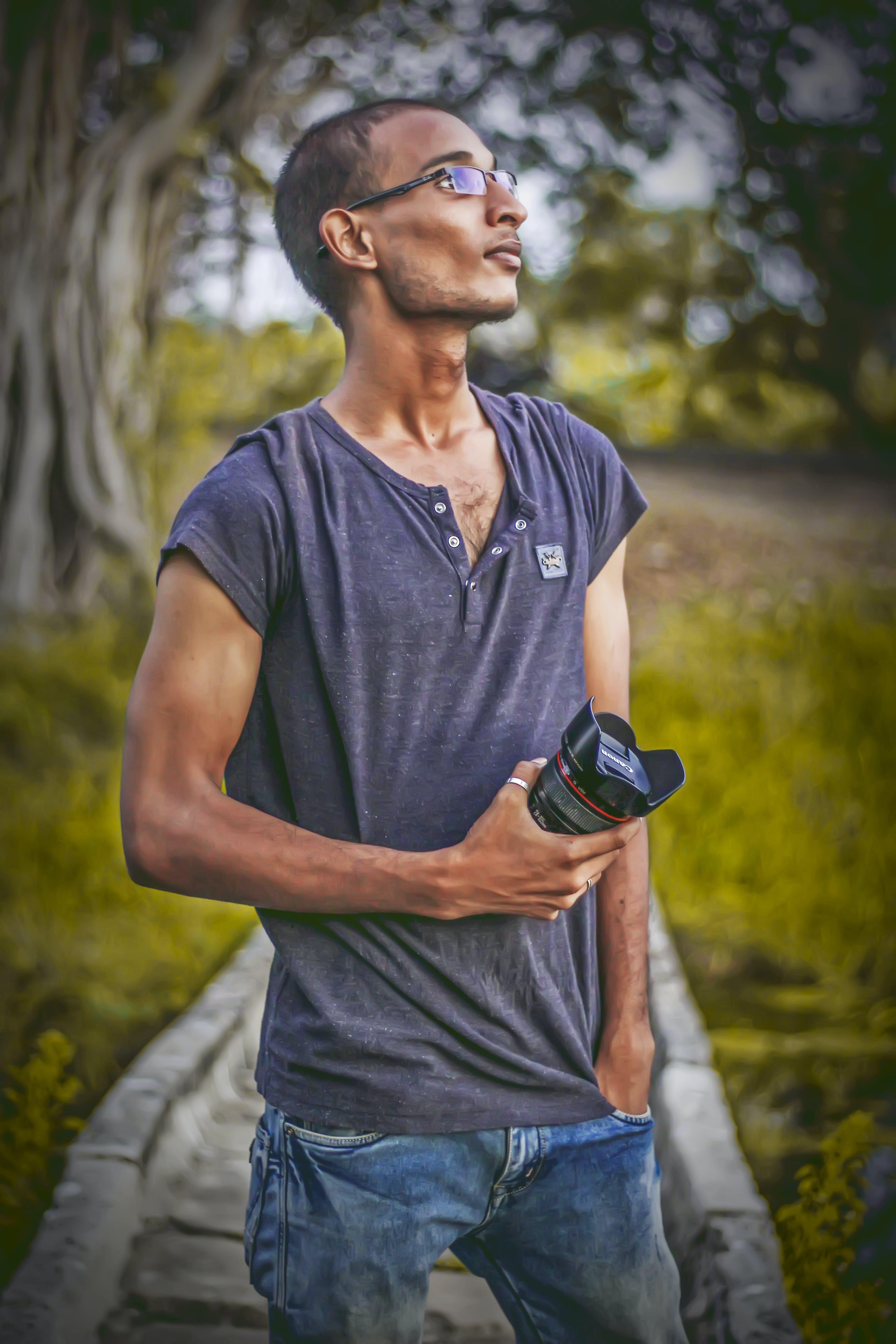 Shallow Focus Photography of Man Wearing Gray T-shirt Holding Dslr Camera Lens