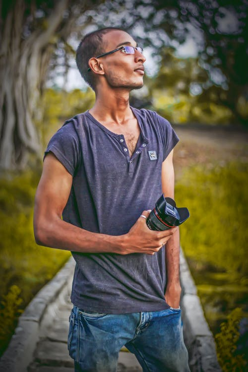 Shallow Focus Photography of Man Wearing Gray T-shirt Holding Dslr Camera Lens