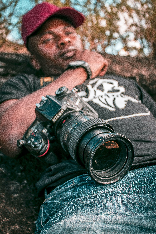 Selective Focus Black Nikon Dslr Camera With Zoom Lens on Lap Photo