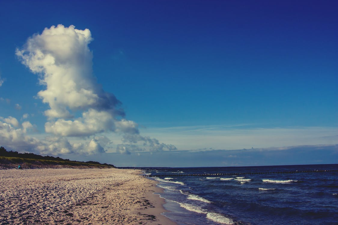 Bodies of Water Beside Sand on White Clouds and Blue Sky