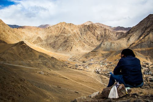 Person Sitting on Mountain Under White Sky