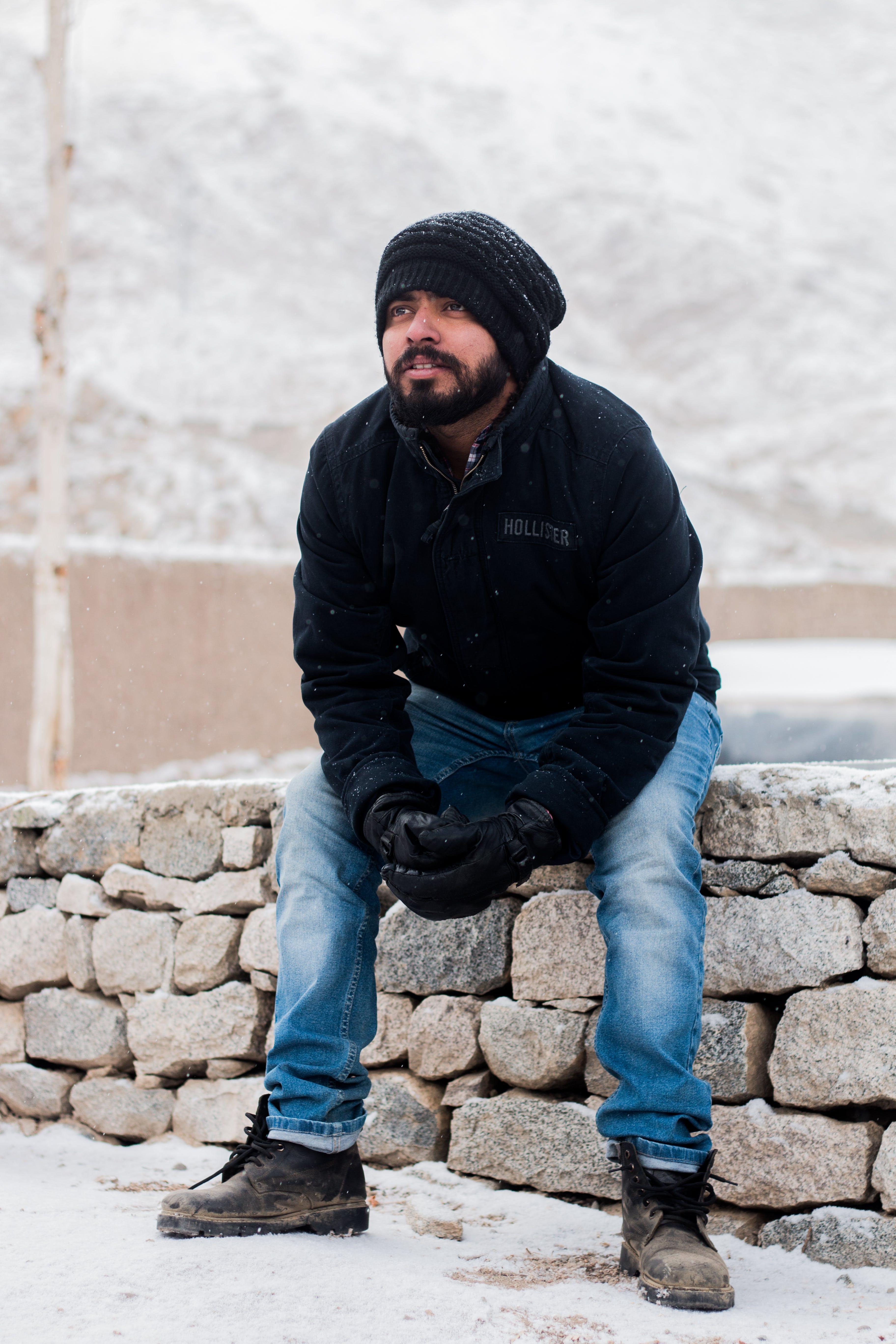 Man Sitting on Rock Wearing Black Jacket