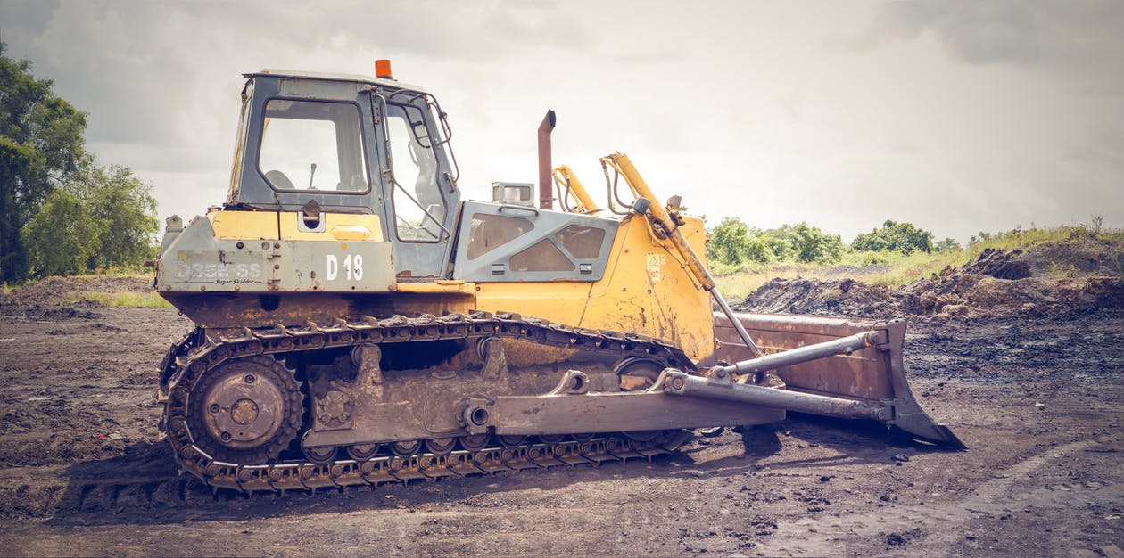 Yellow and Brown Metal Pay Loader on He Dirt