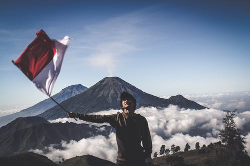 Man Wearing Black Crew-neck Sweater Holding White and Red Flag Standing Near Mountain Under Blue and White Sky