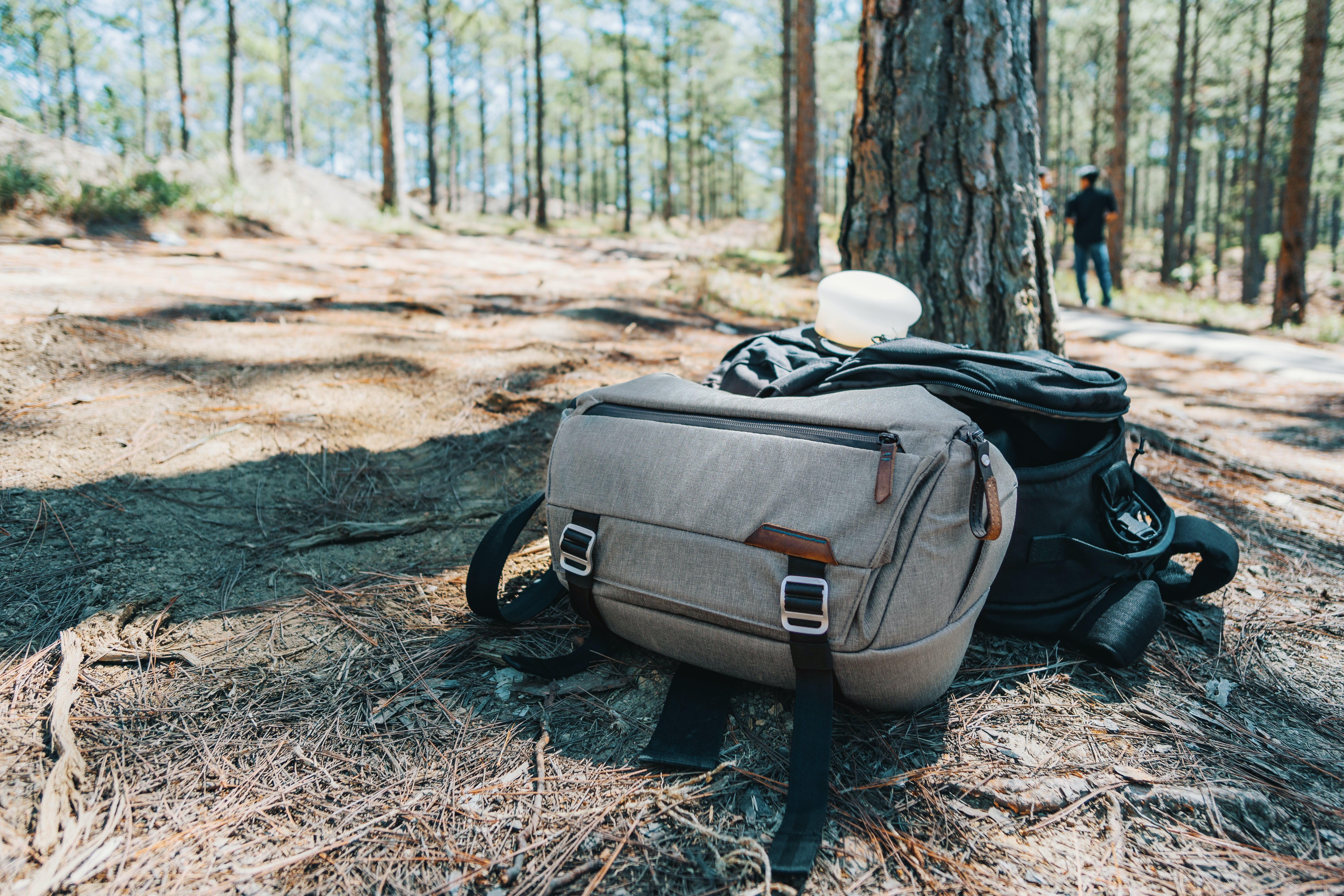Photograph of Two Duffel Bags Under the Tree in Forest