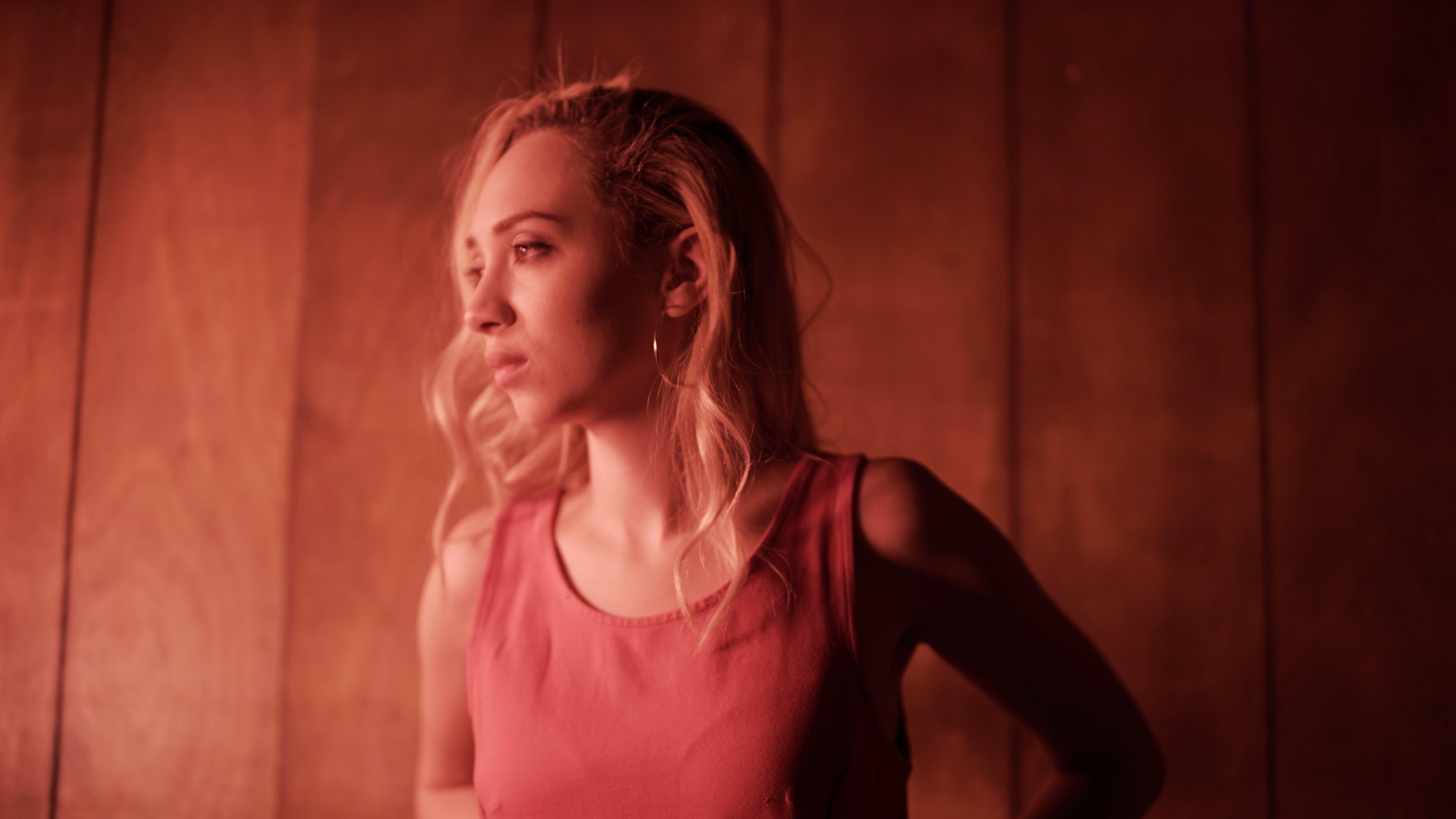 Woman Wearing Pink Sleeveless Tops Standing Near Brown Wooden Wall