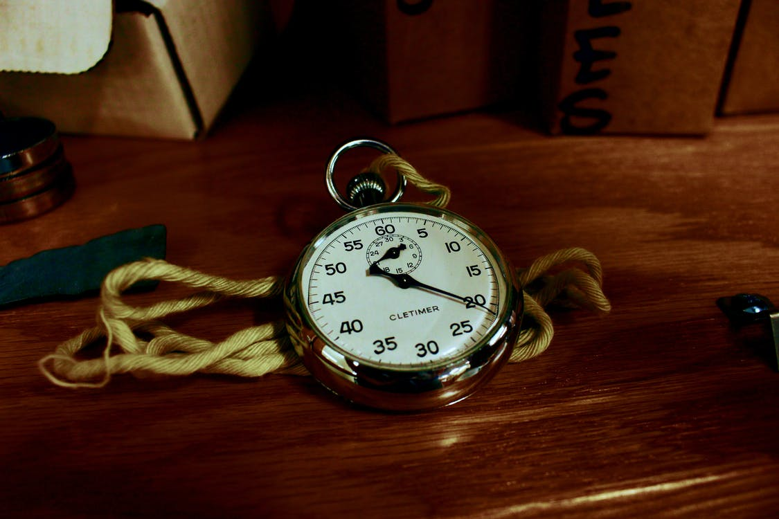 White Pocket Watch With Gold-colored Frame on Brown Wooden Board