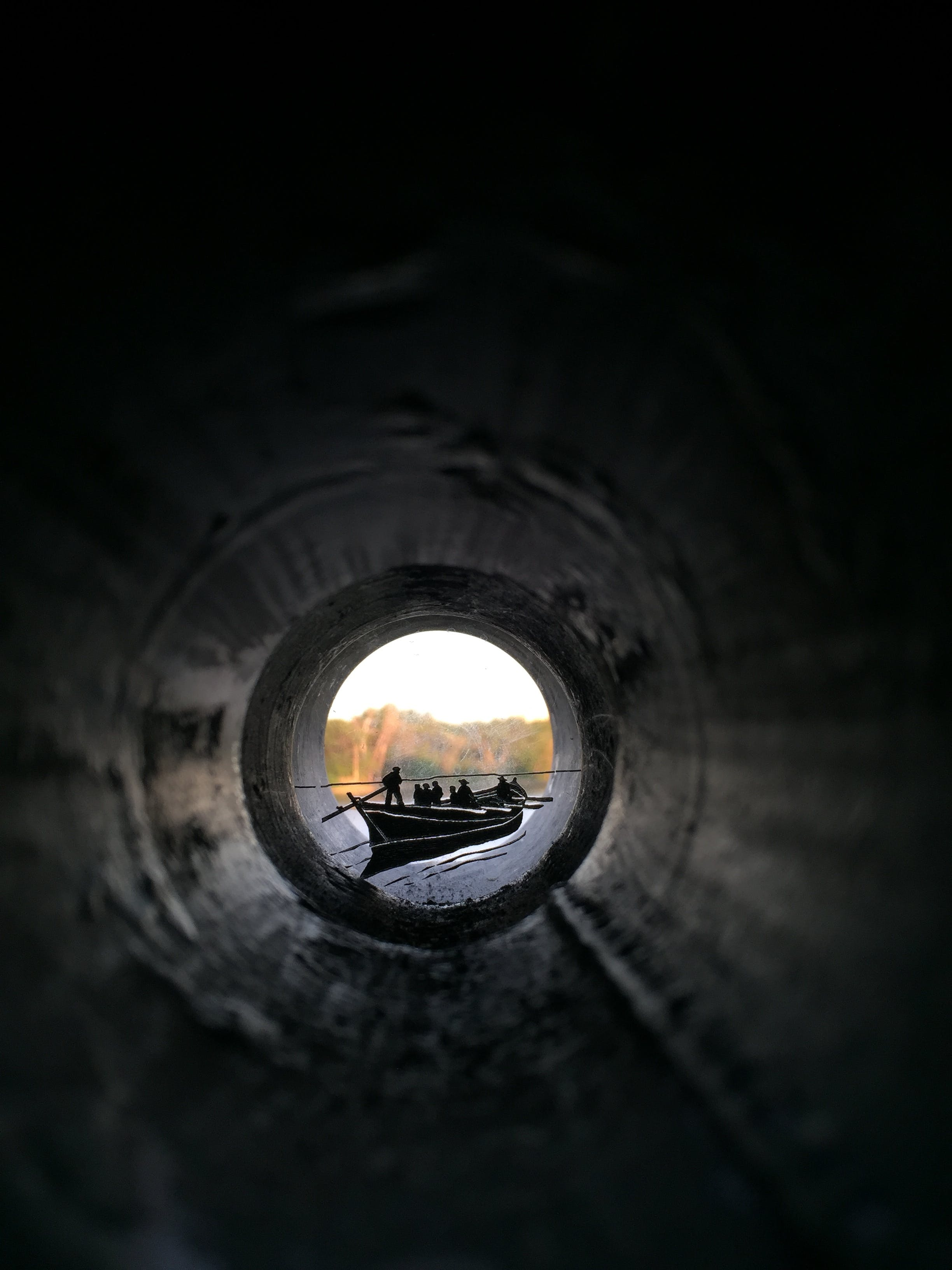 People Riding Canoe Boat View from Inside Pipe